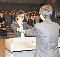 関西外国語大学の学位記授与式で、学部生を代表して学位記を受け取る林慎也さん=9月6日、同大学の中宮キャンパス(同大学提供)