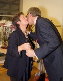 remise de médaille légion d'honneur élu remet la médaille et embrasse la femme décorée en intérieur