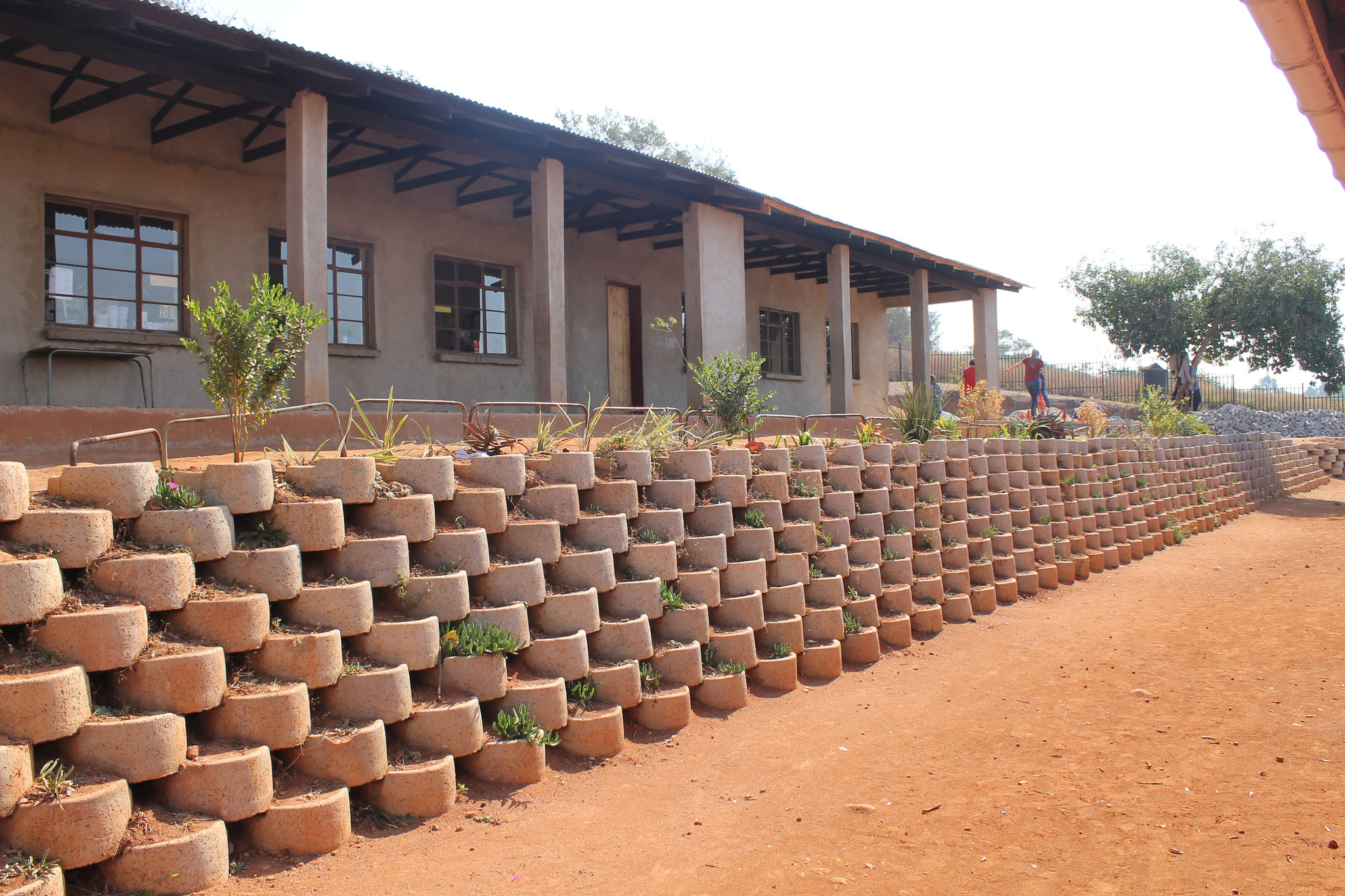 das neue Schulgebäude mit der Stützmauer