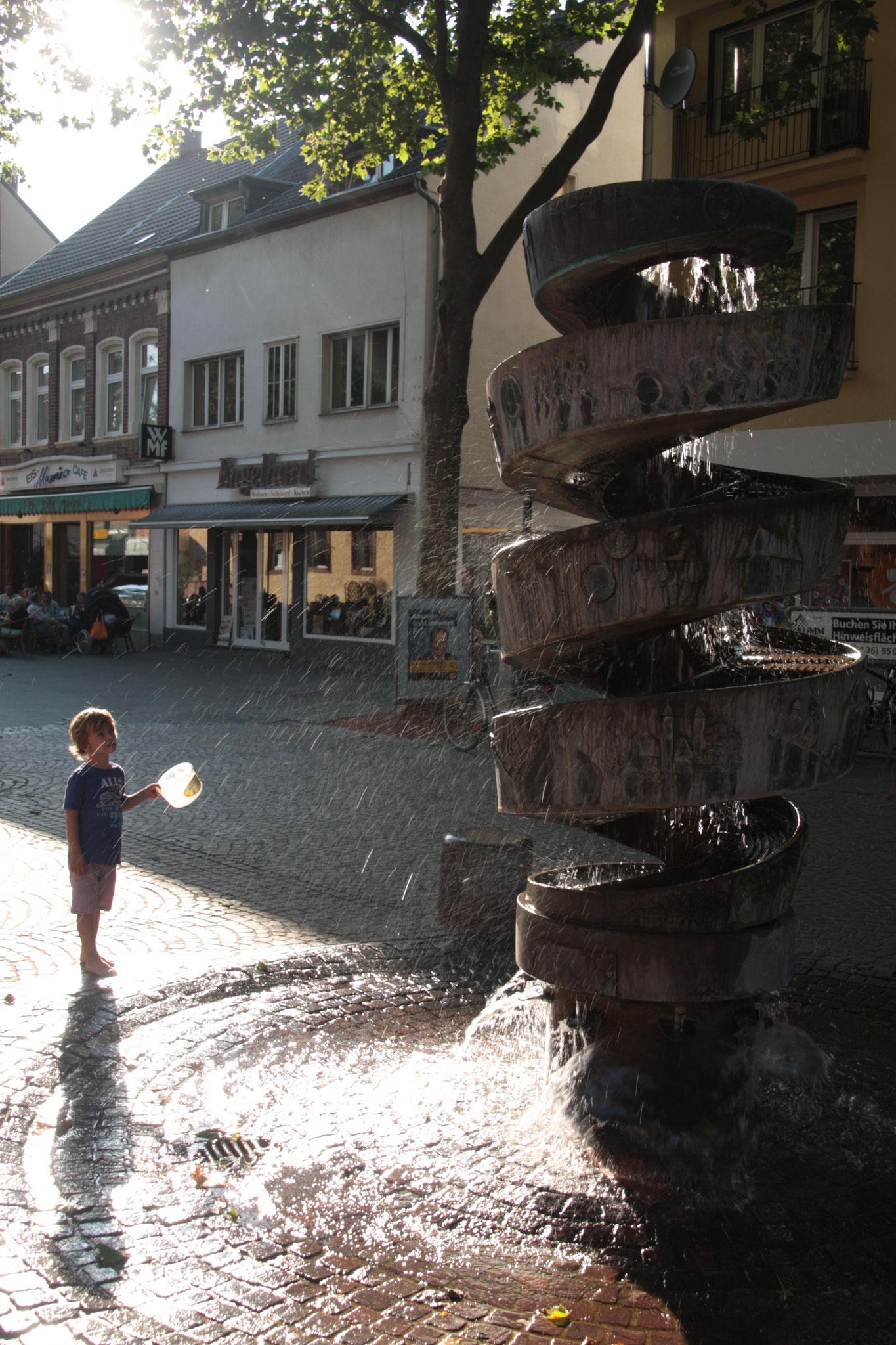 Junge am Brunnen