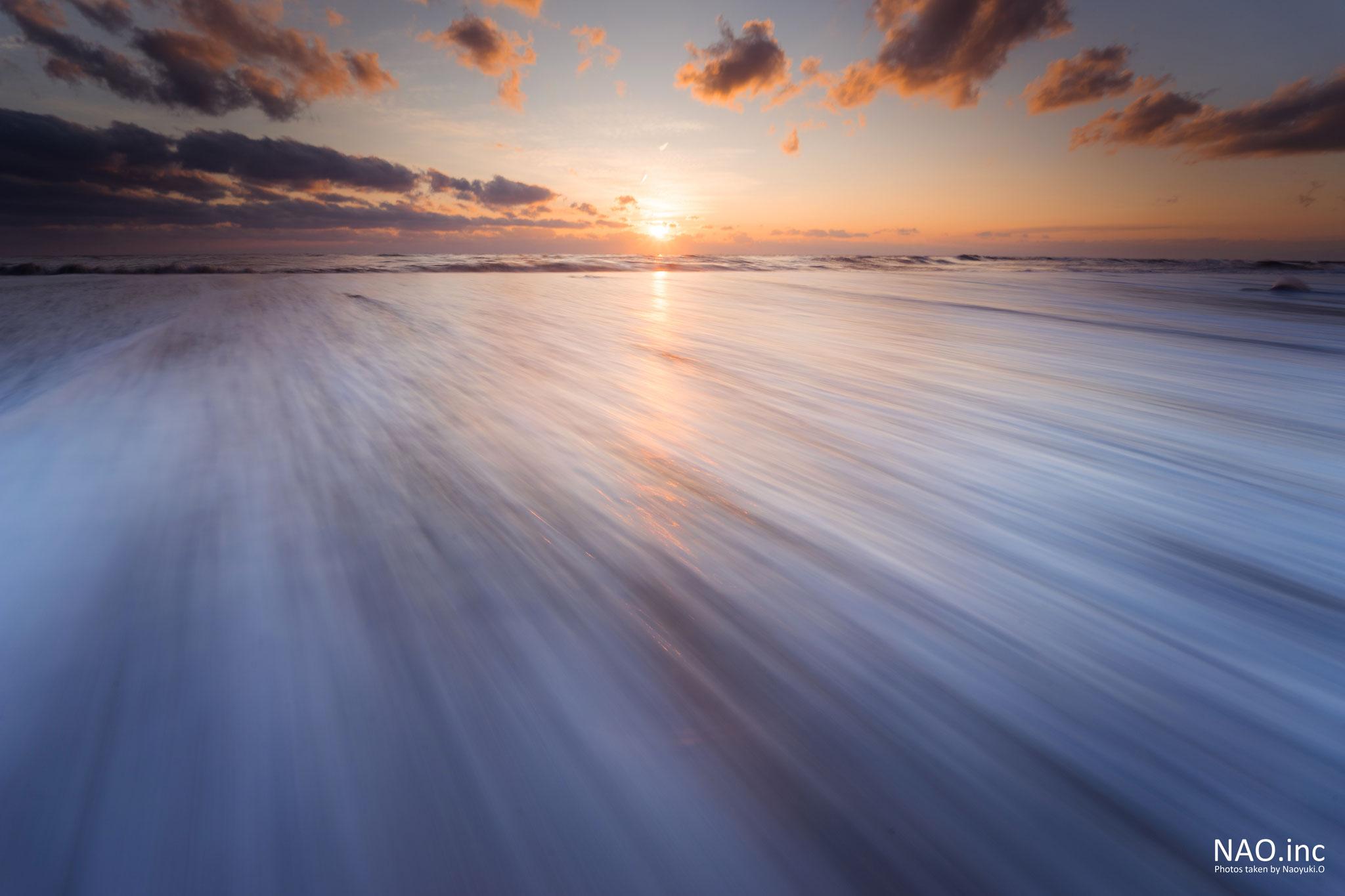 むかわ町の海岸。浜辺に押し寄せる波が夕日に色づく。