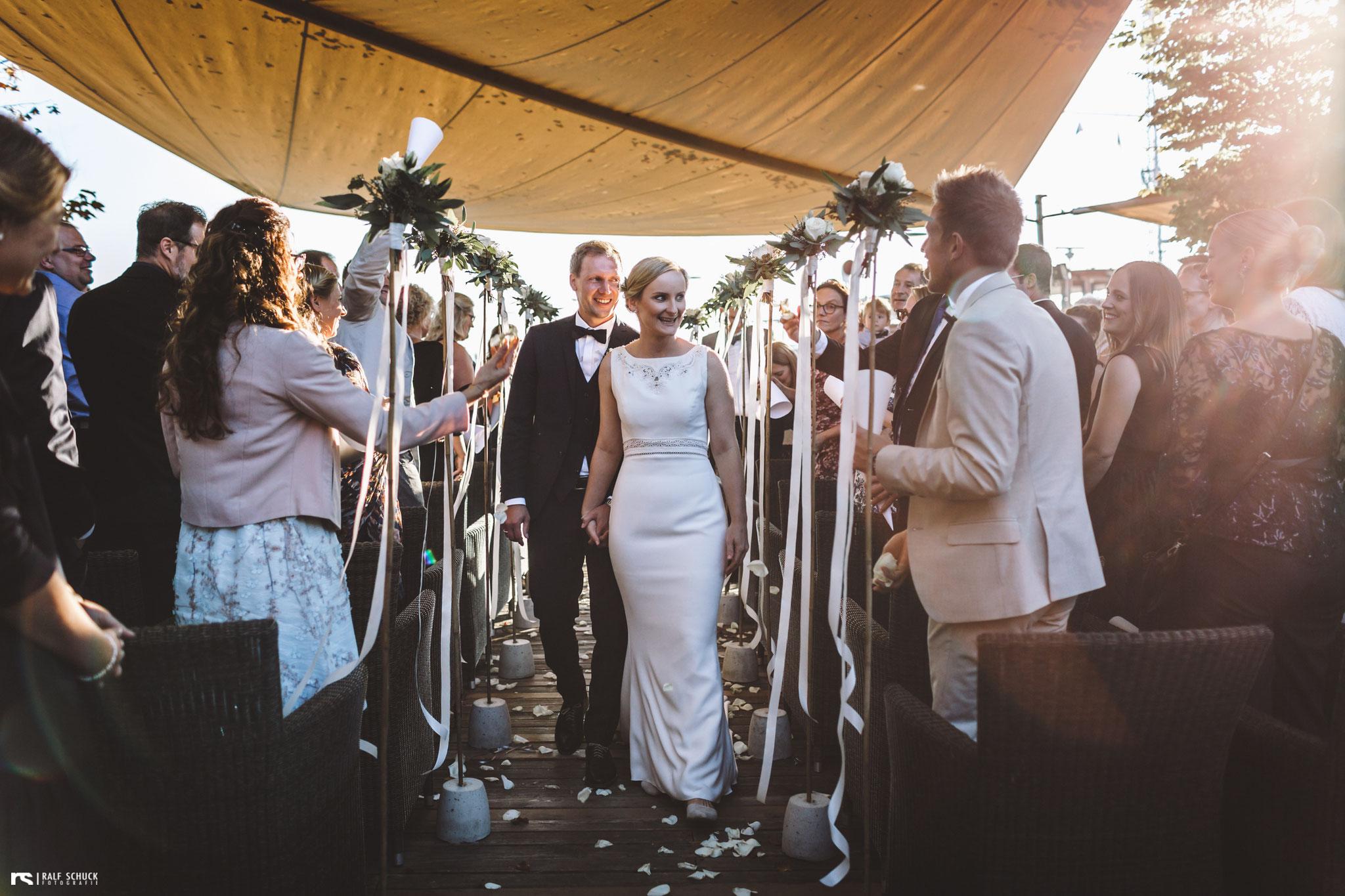 Die beiden ziehen glücklich vermählt durch die Festgesellschaft, um beim anschließenden Sektempfang auf die Trauung anzustoßen (Foto: Ralf Schuck)