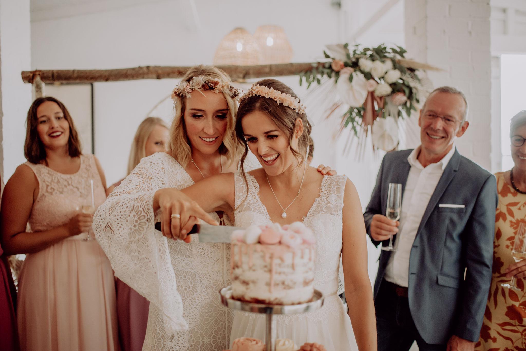 Anne & Antje schneiden stolz ihre Hochzeitstorte an (Foto: Landei Fotografie)