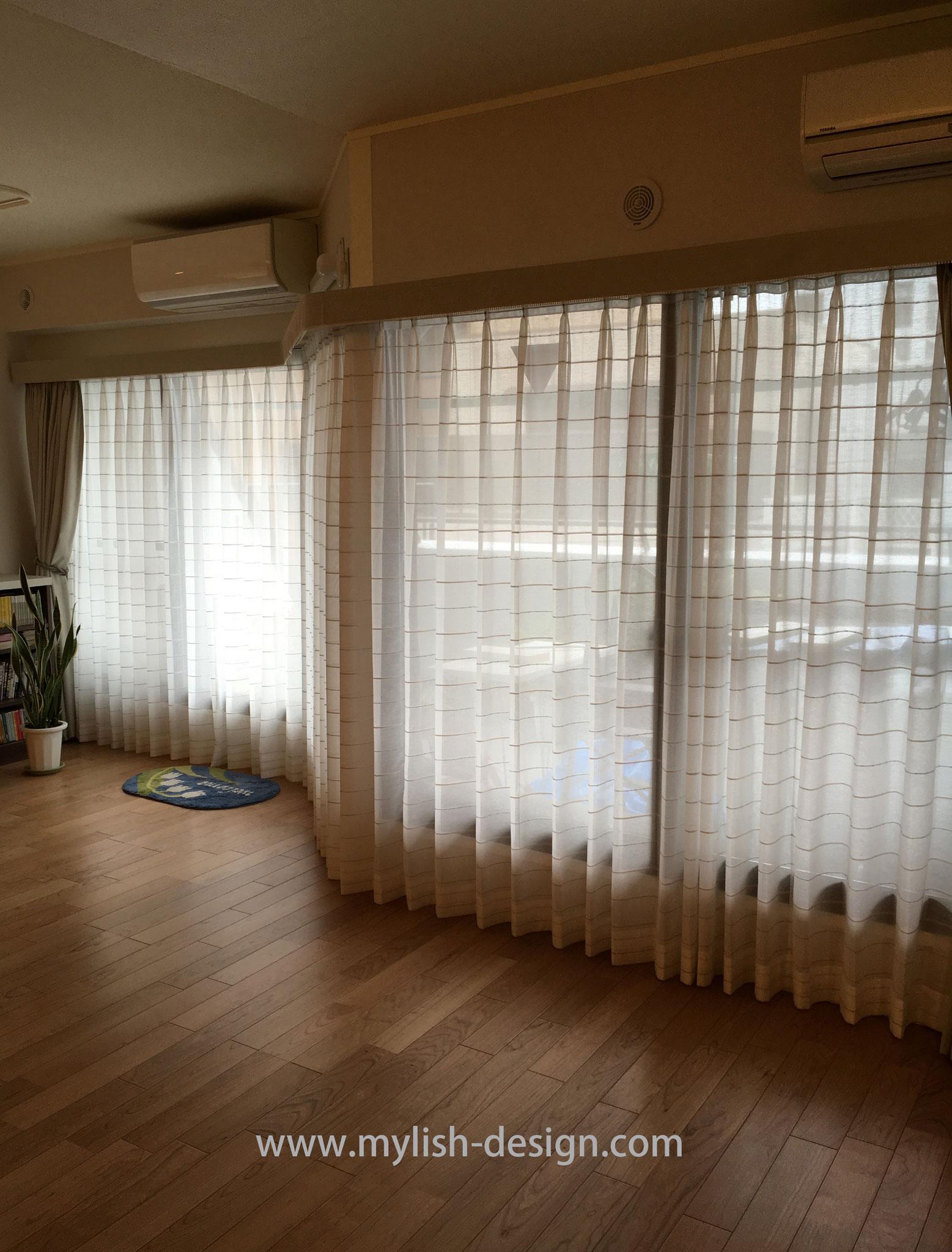 カーテンは2倍ヒダのレギュラーカーテン(カワシマセルコン)を両開きで。全ての窓をつなげてレールを現場で曲げて設置したので、とても美しい窓になりました。