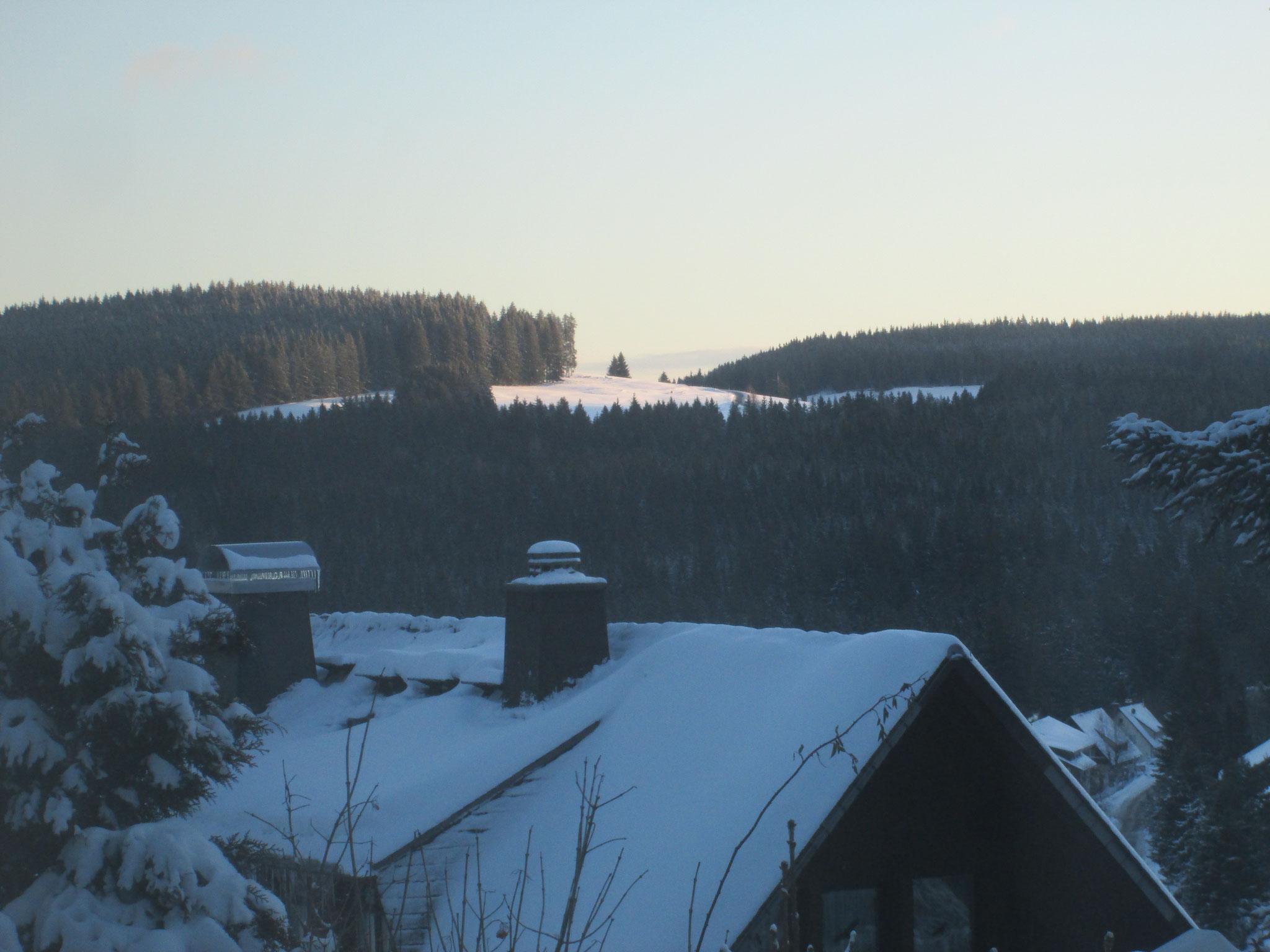 Der Ausschnitt, den ich festhalte, rosa Morgenlicht auf einer entfernten Schneefläche,