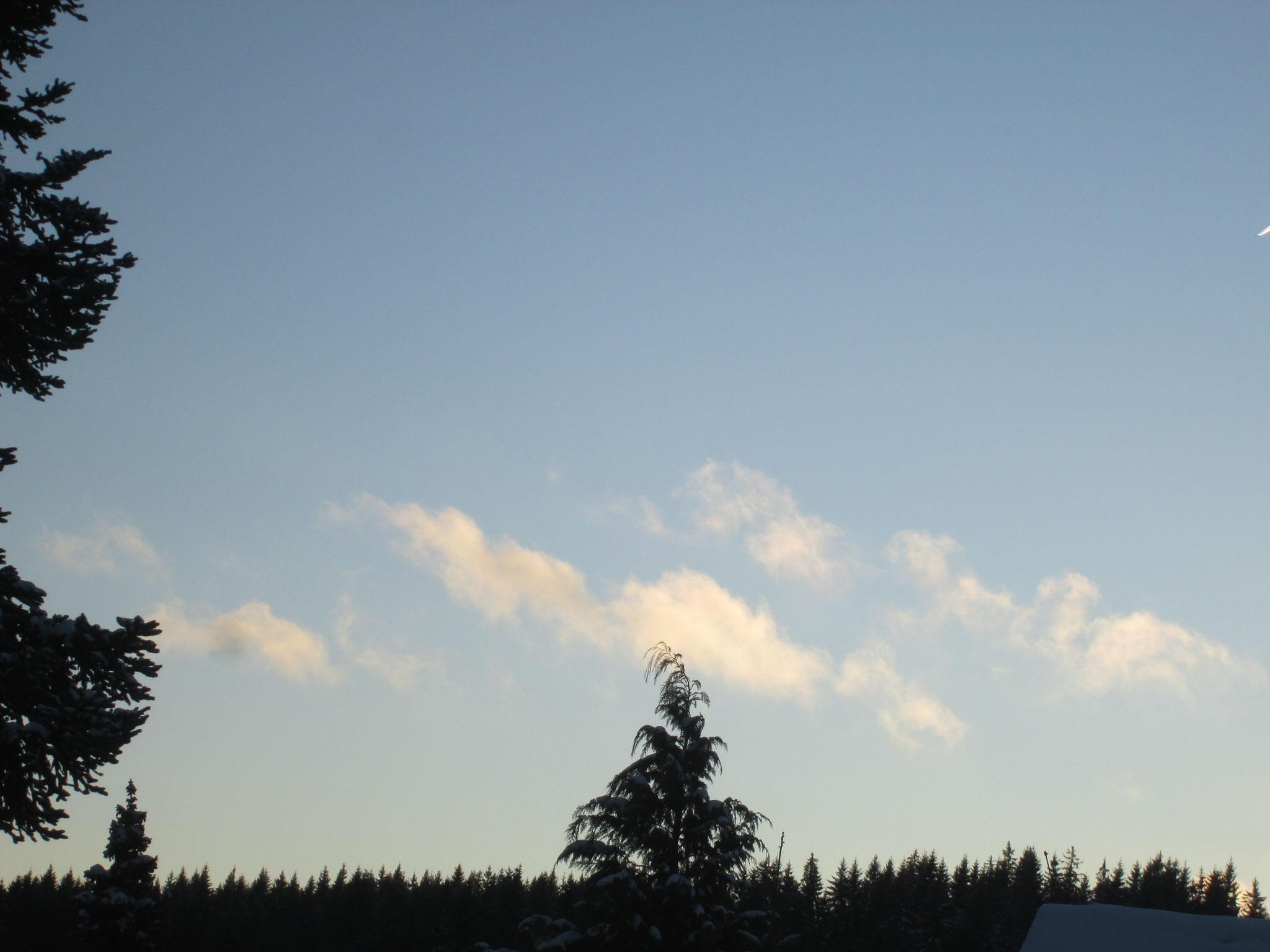 pastellene Wattewölkchen vor glasblauem Himmel