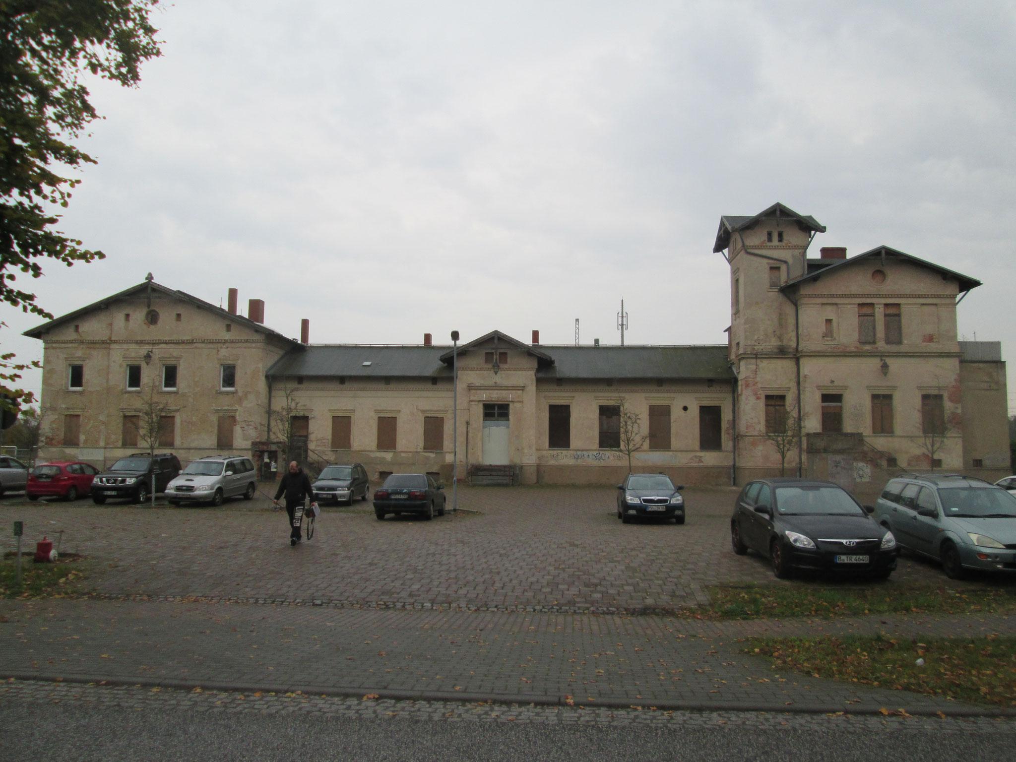 Ich trete aus einem ruinösen Bahnhof mit verrammelten Fenstern auf die menschenleere Landstraße.