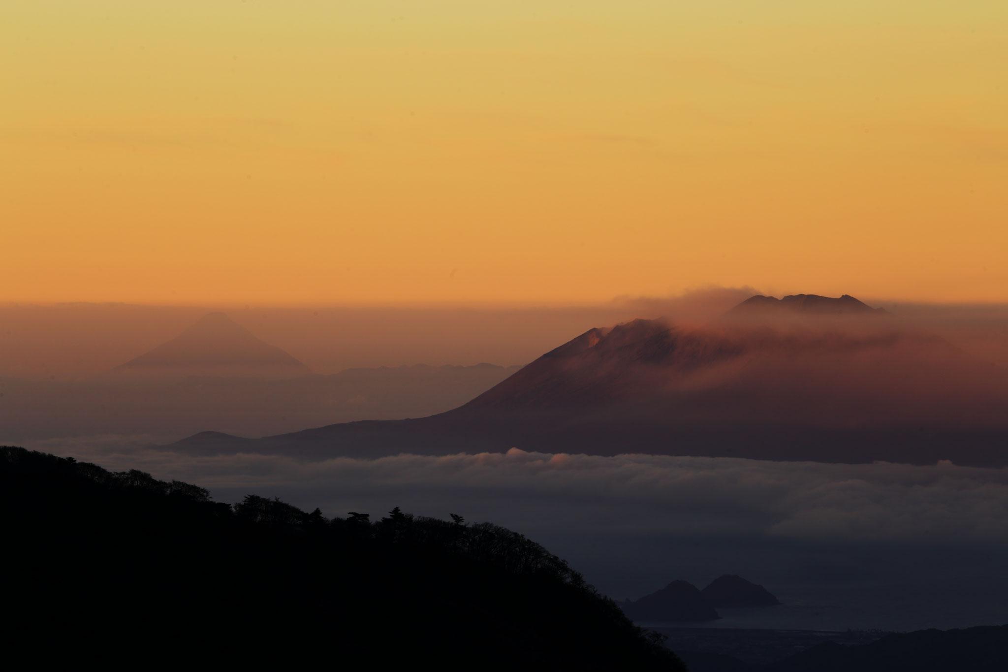 朝焼けに浮かび上がる開聞岳(左)と桜島(右)えびの高原白鳥山