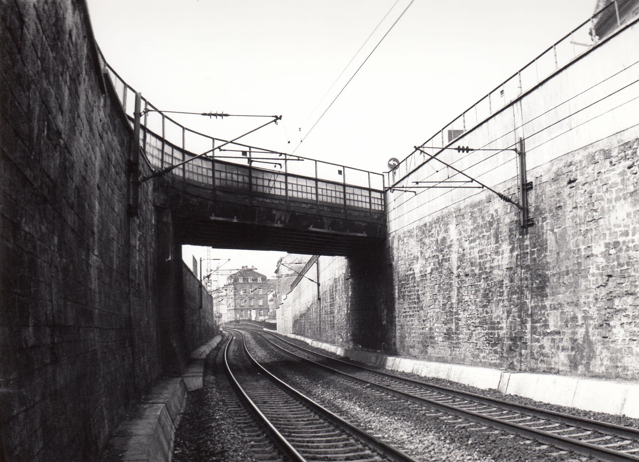 Bahn unter Fischerrainbrücke, hinten Eckhaus zwischen Mainaussicht-Fischerrain