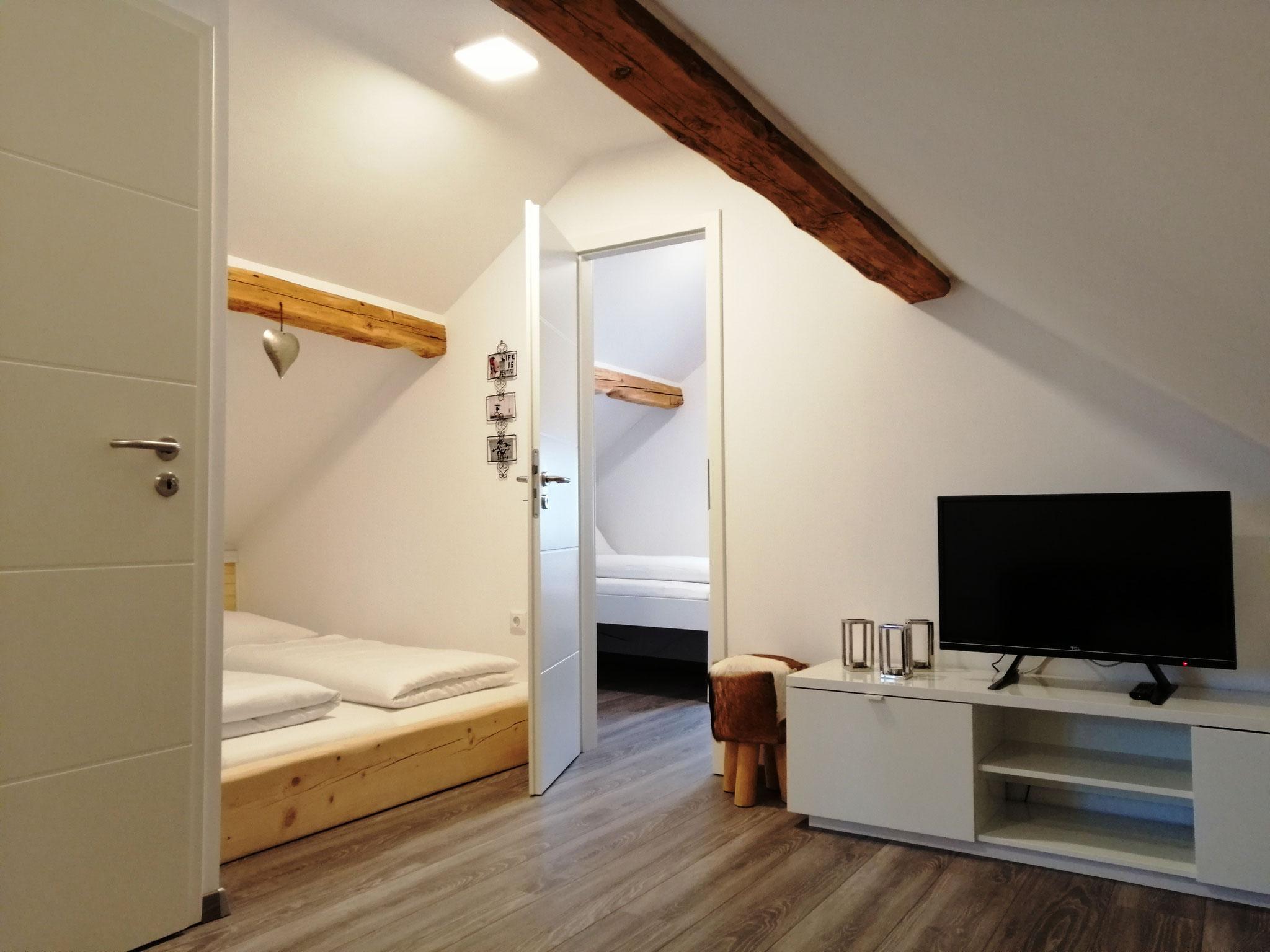 Blick von der Couch auf Doppelbett und zweites Schlafzimmer
