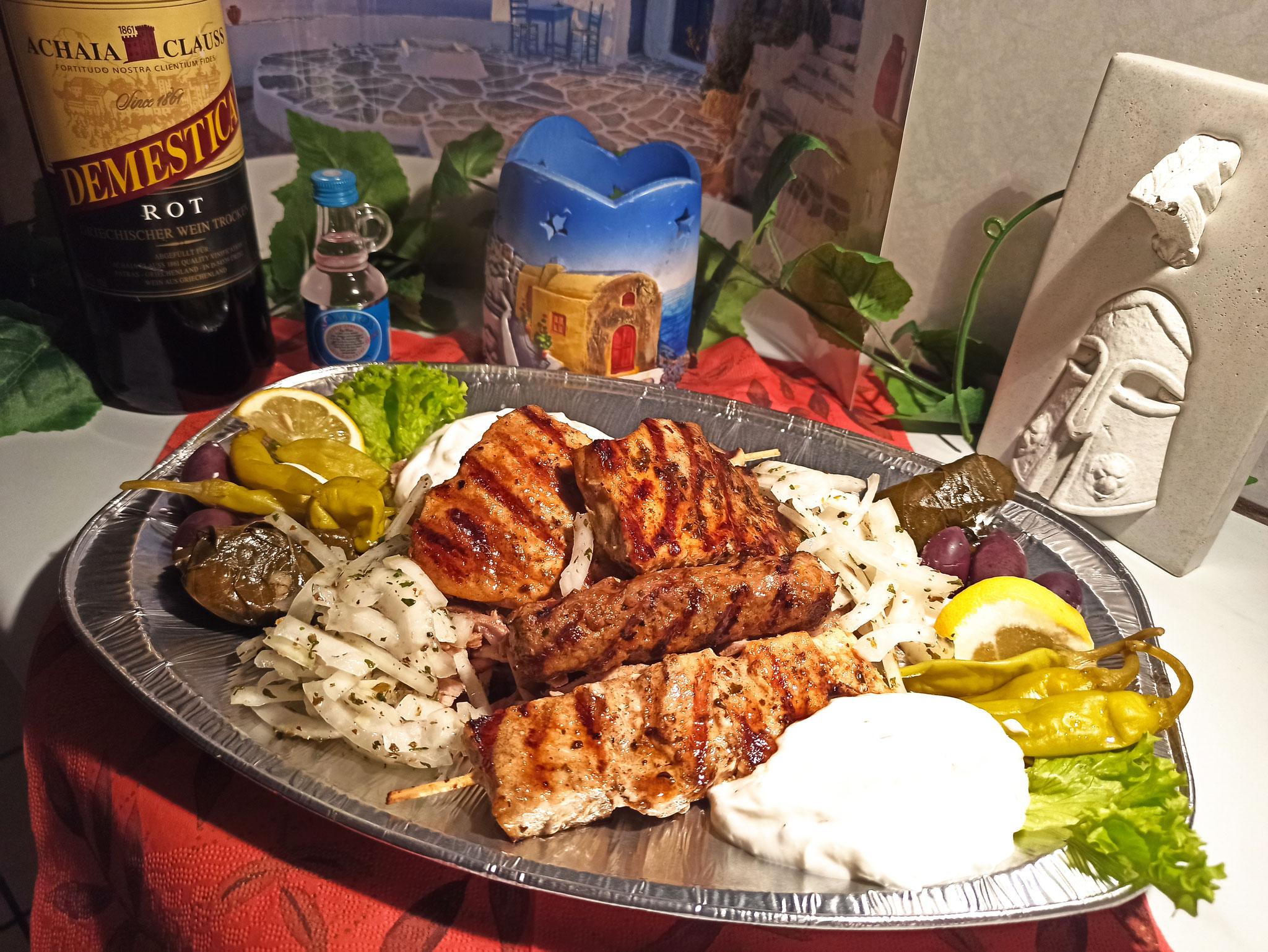 Unsere Grillplatte für zwei Personen: 4 Sorten Fleisch, Weinblätter, Peperoni, griechische Oliven, dazu Pommes oder Reis und Salat