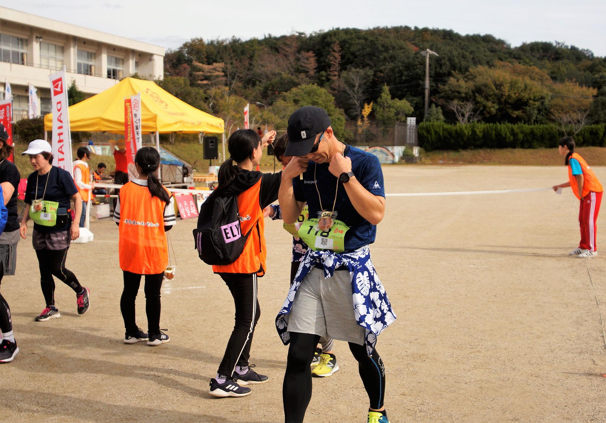 ゴール後、魚太郎さんのアイデア、どら焼きメダルを、布土小学校の子どもにかけてもらいました。
