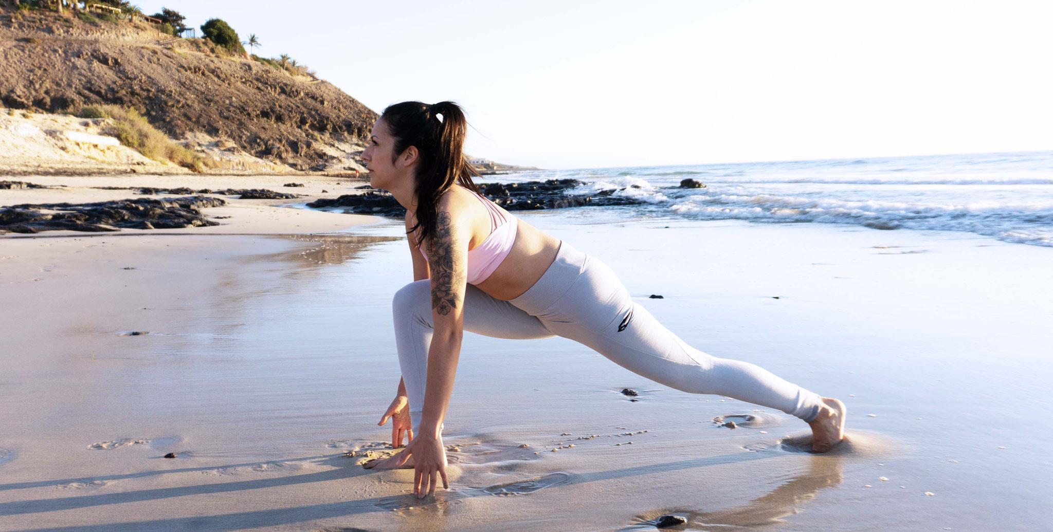 Atme ein und bringe ein Bein nach vorne,  zwischen deine Handflächen. Öffne dich nach vorne