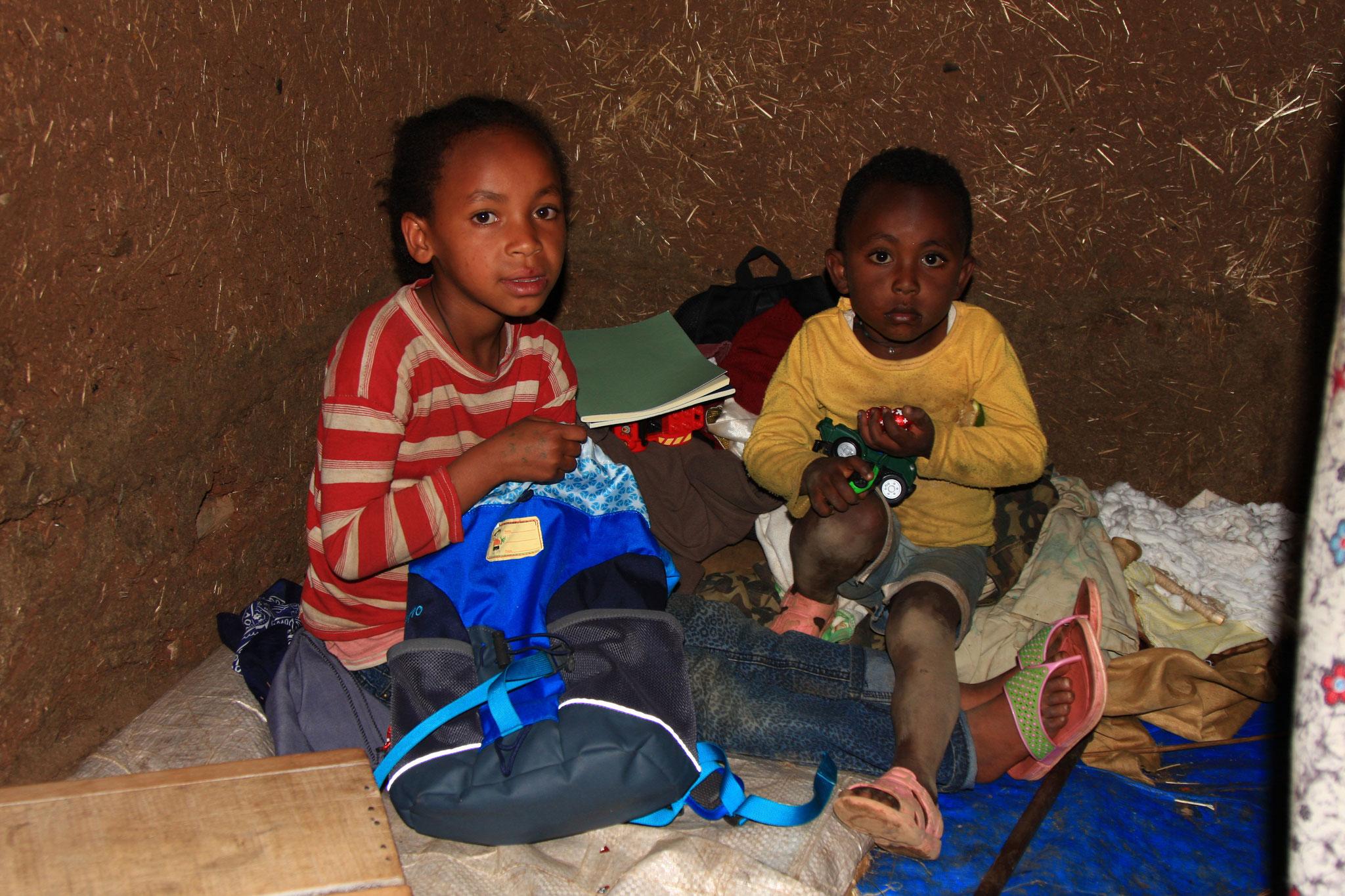 Kinder bekommen Schulmaterial und Taschen.