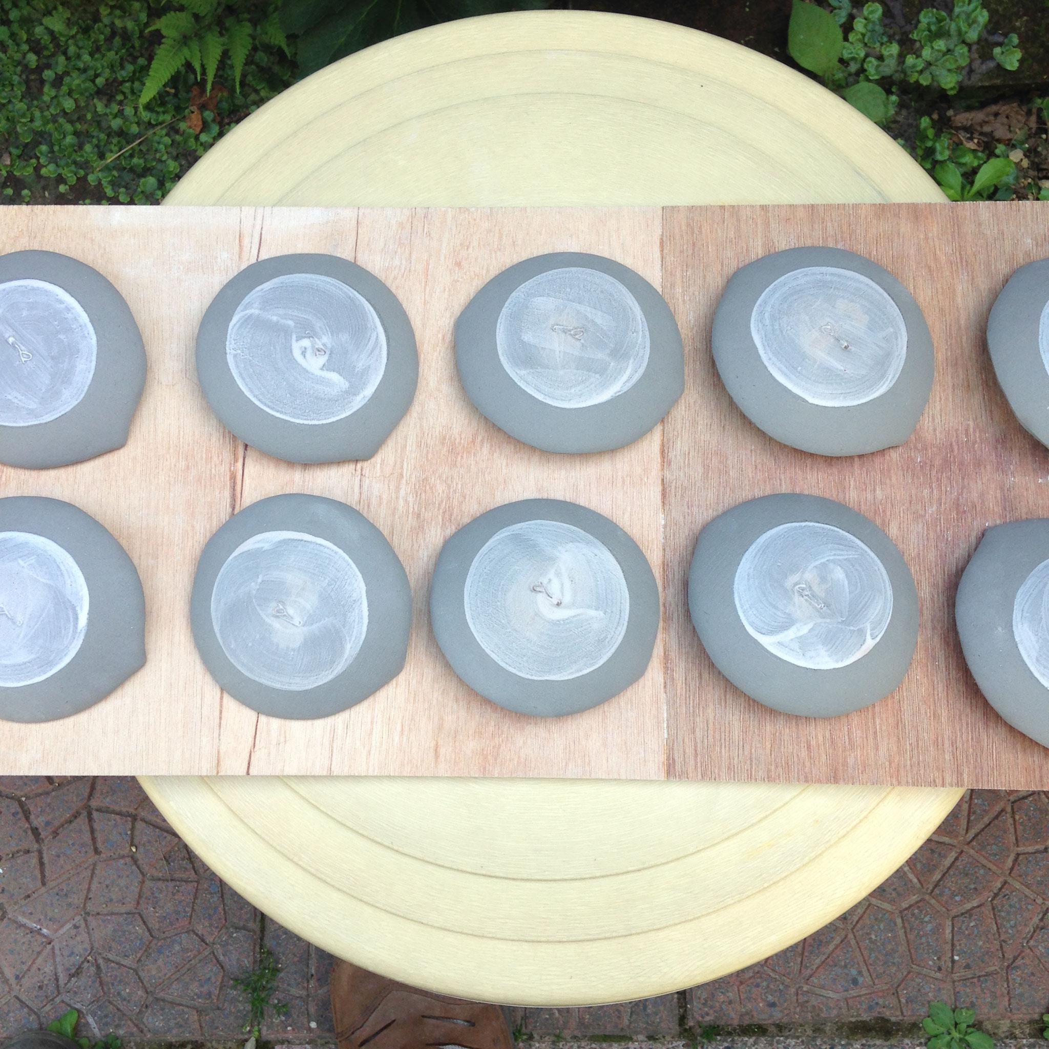 器の裏に釉薬がつかないように、撥水剤(ロウのようなもの)を塗り、釉薬を掛けます