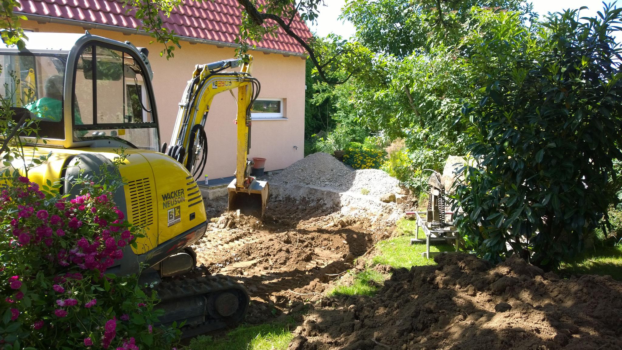 der Bagger gräbt die Grube für die Fundamentplatte