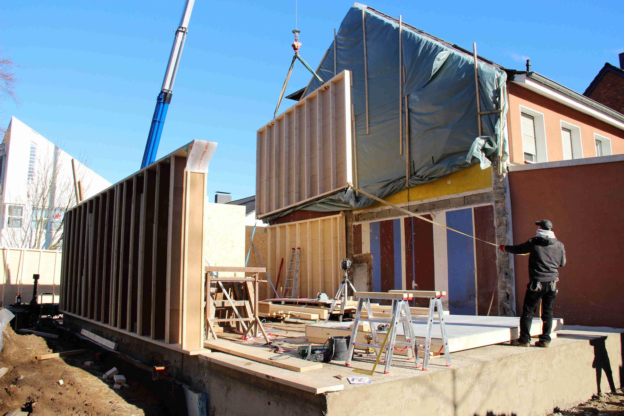 Baubeginn beim Ausbauhaus in Köln Weiden: Wir heben die vorproduzierten Holzrahmenbauwände mit dem Kran an ihren Platz.