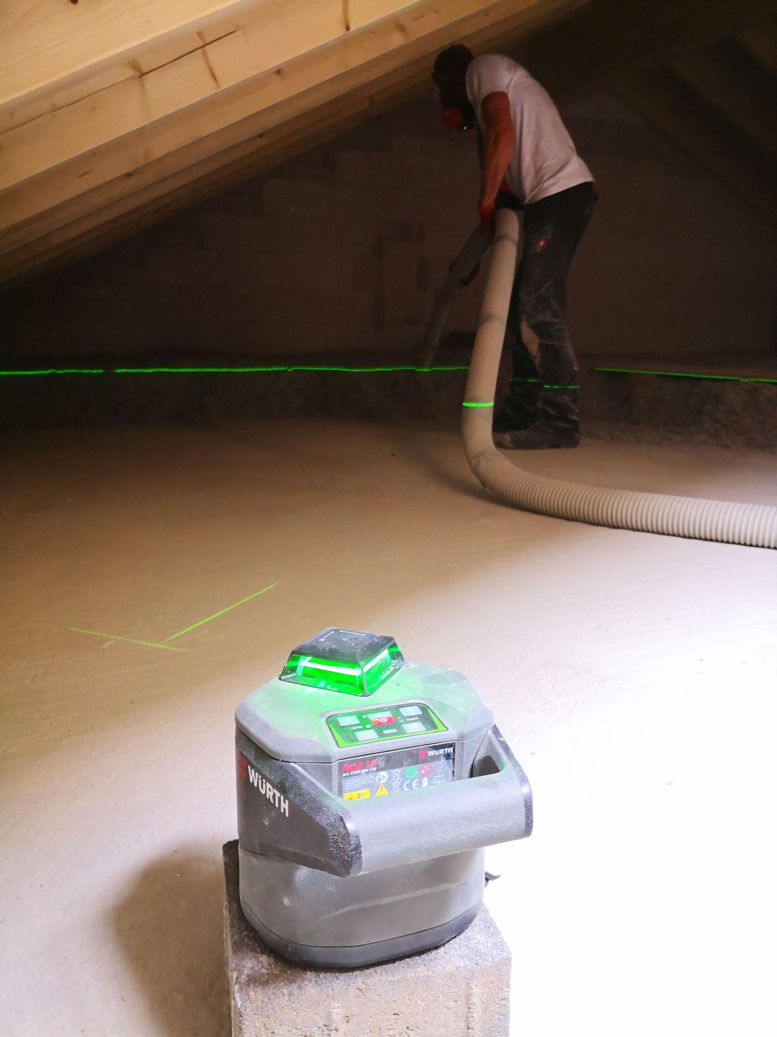 Beim Aufblasen von Zellulosedämmung auf die oberste Geschossdecke hilft ein Lasergerät zum Bestimmen der richtigen Dämmstärke.