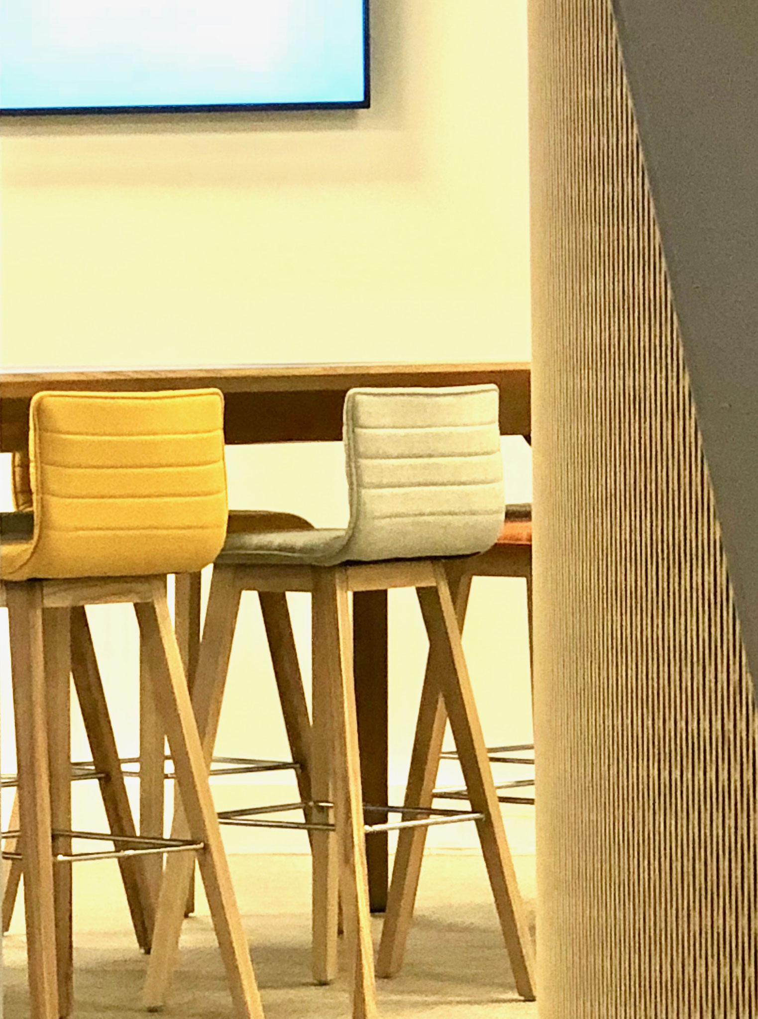 Une table haute pour des réunions, assortie de chaises hautes en flanelle pour le confort des collaborateurs.