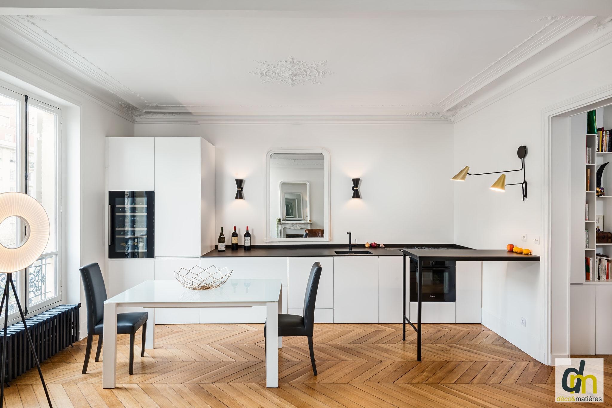 une cuisine dans un séjour haussmannien : Elle se fond dans la décoration haussmannienne. Façades blanches et plan extra fin en céramique anthracite