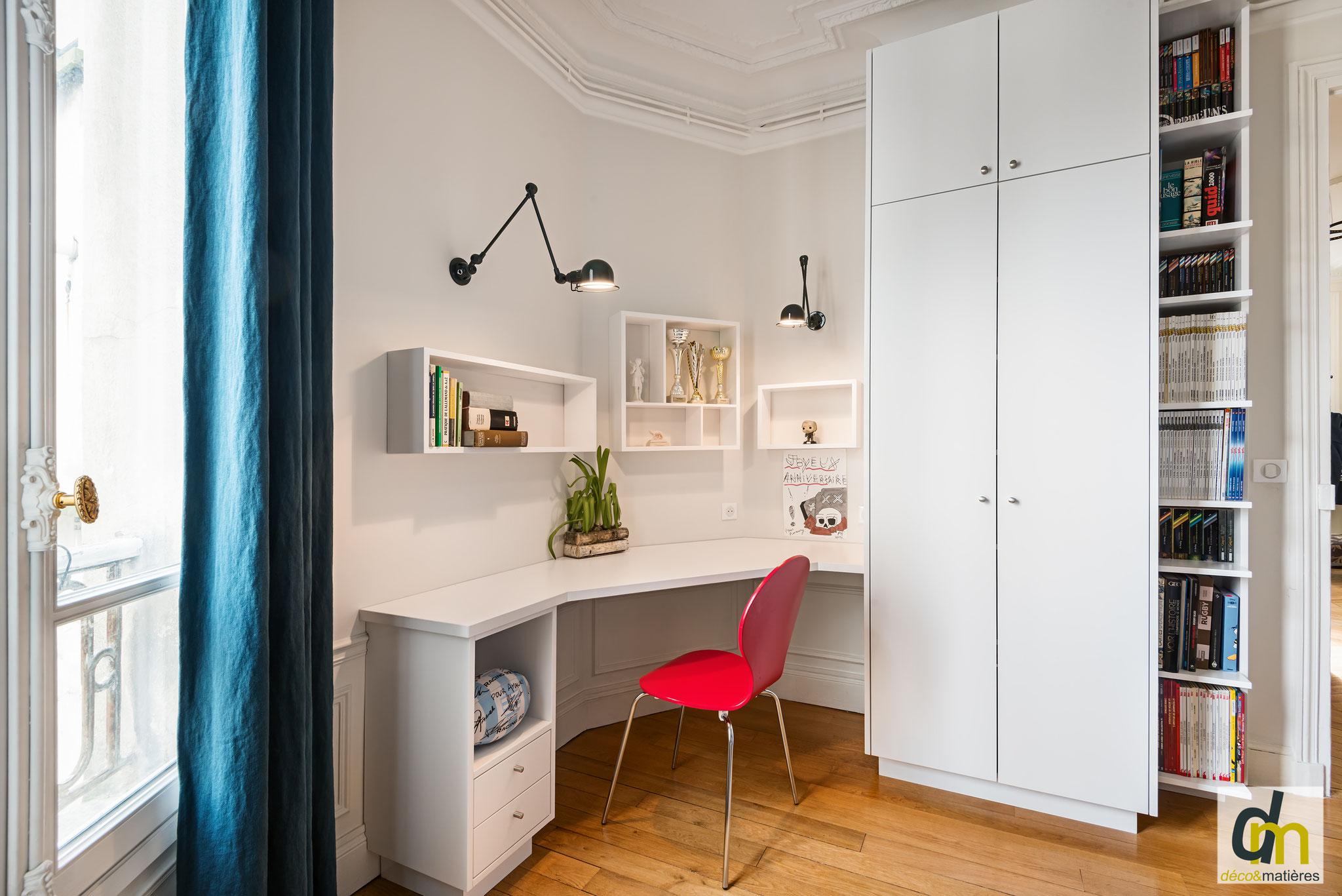 Un bureau sur mesure dans un espace enfant, avec étagères murales, armoire et bibliothèque. Aménagement réussi dans un espace restreint.