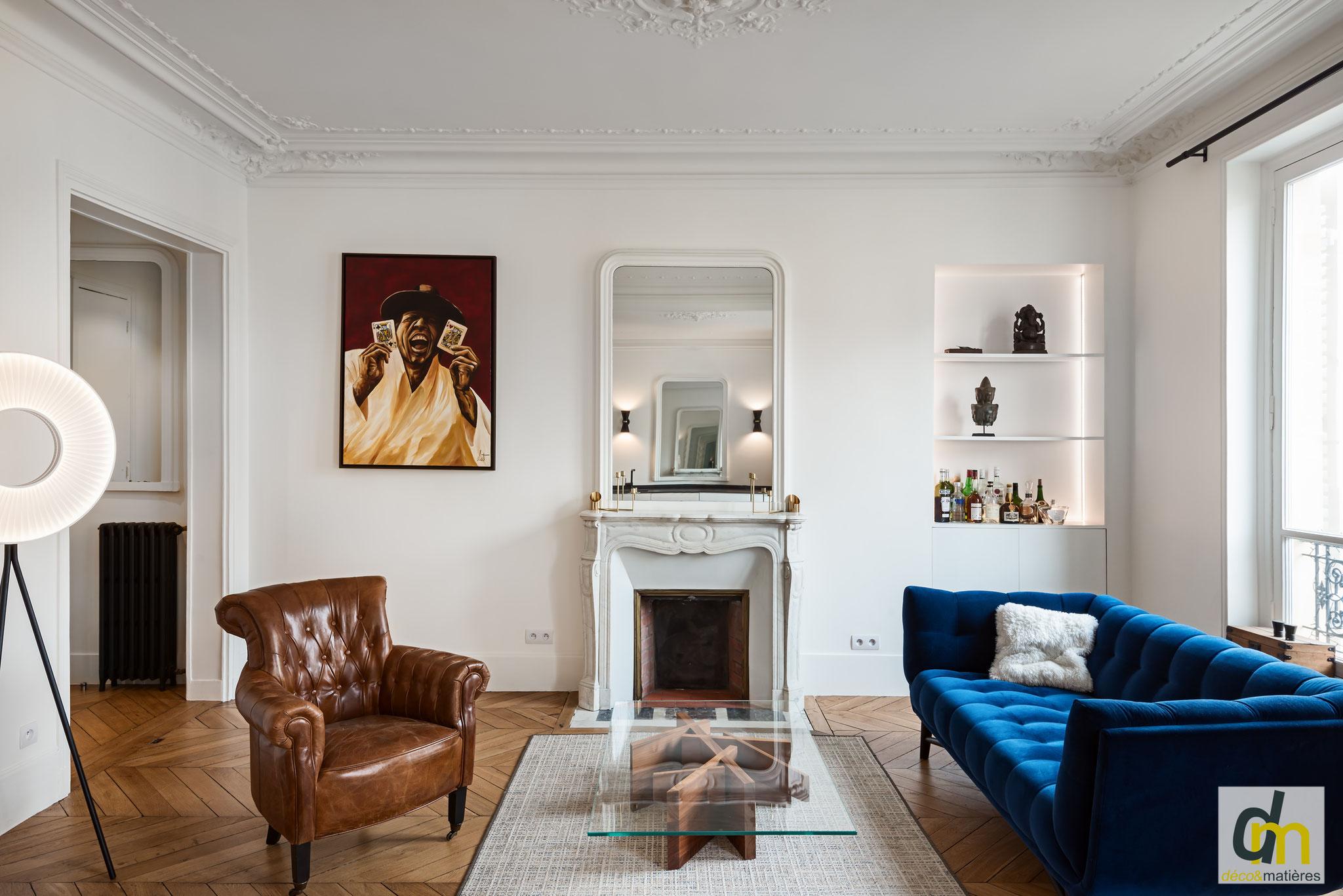 Un salon haussmanien, avec cheminée en marbre blanc, niche, et canapé RocheBobois