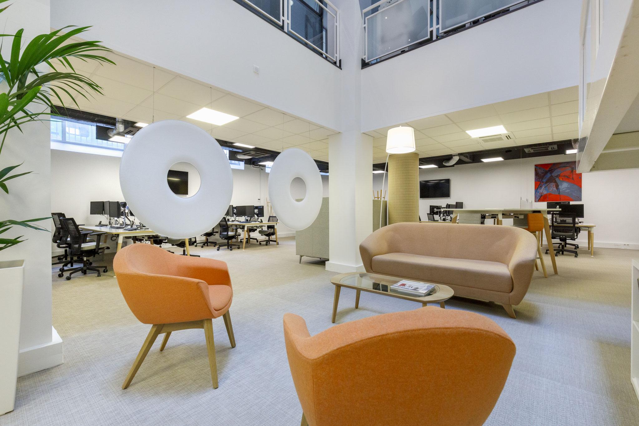 un salon d'accueil dans un espace de co-working, avec du mobilier confortable et contemporain aux couleurs de l'entreprise