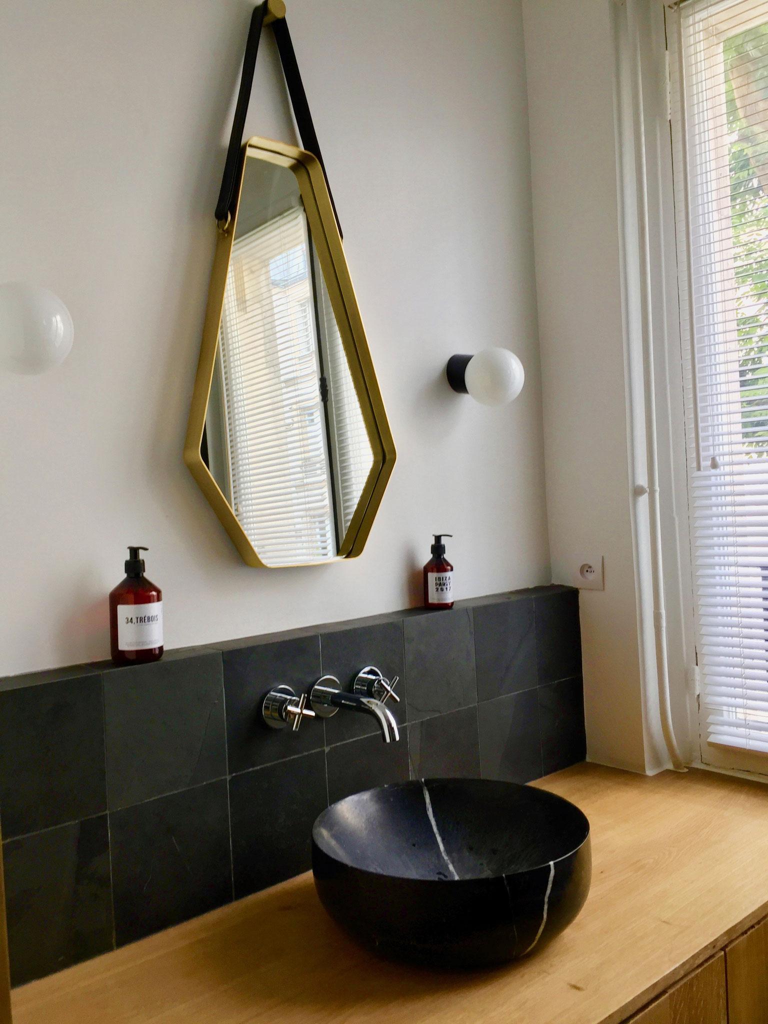 Un miroir laiton, des appliques anciennes, de l'ardoise, du marbre noir en harmonie avec du mobilier en chêne brut