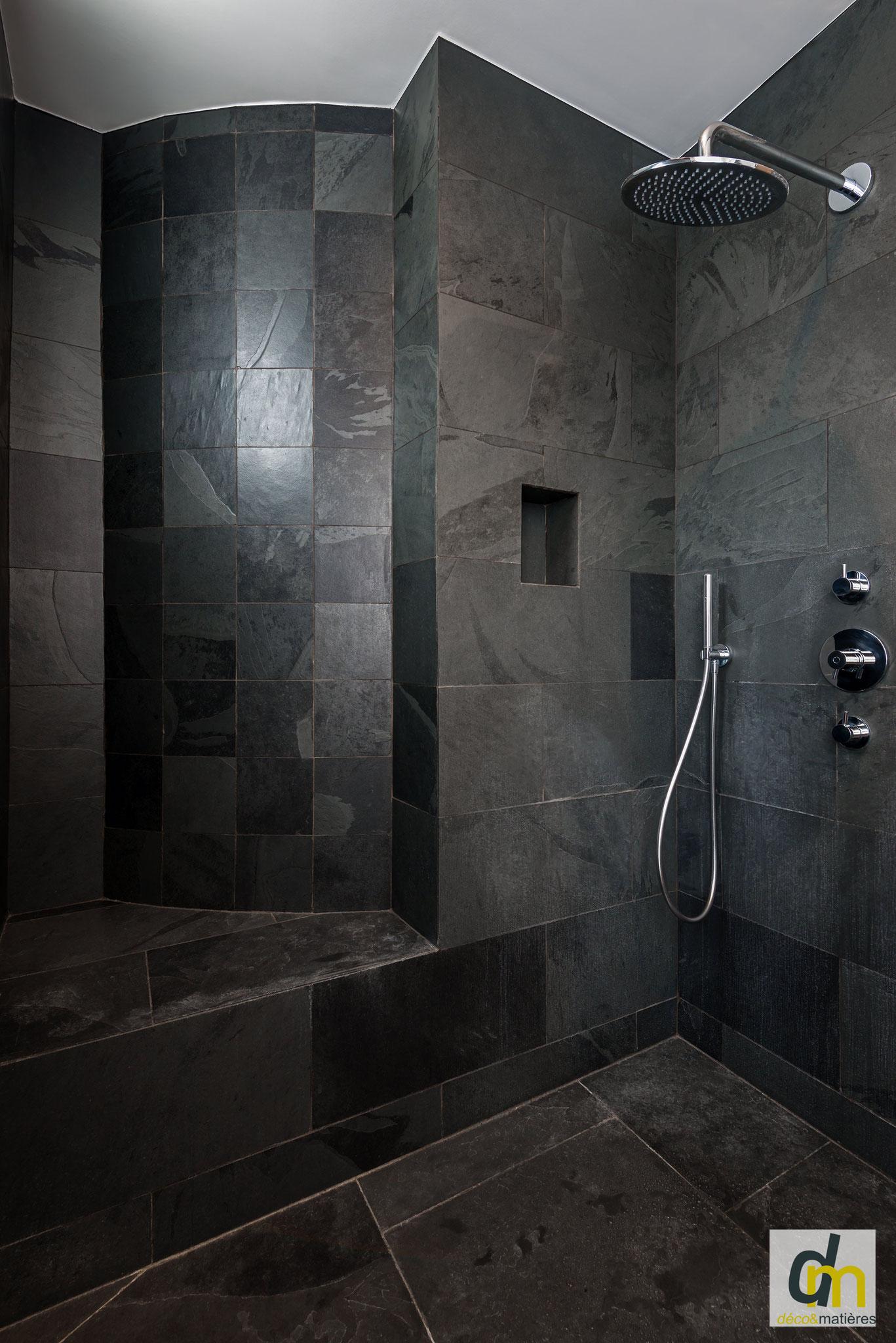 Un espace douche à l'italienne entièrement recouverte d'ardoise noire avec une paroi en verre intégral