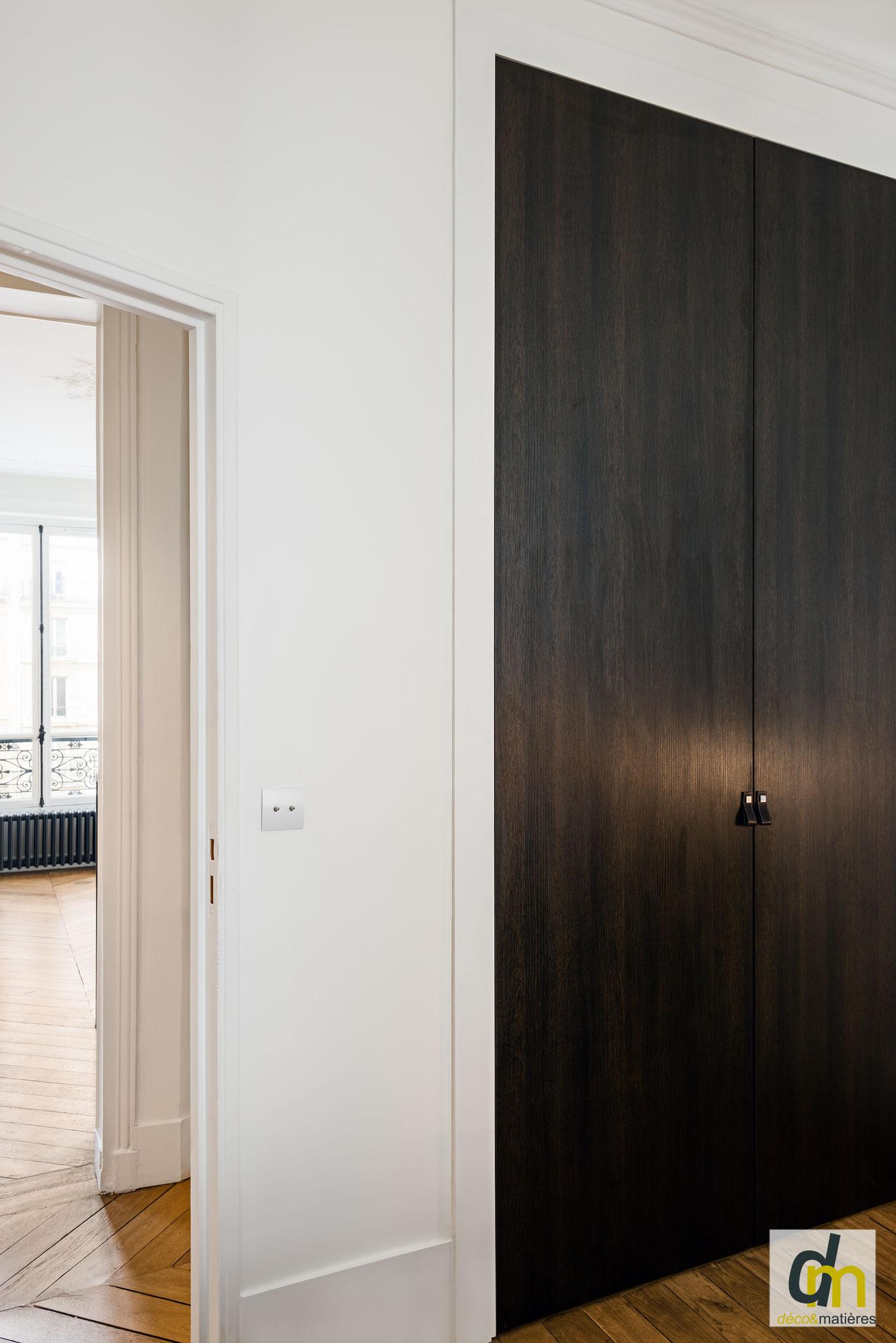 Dressing sur mesure dans chambre d'homme, en placage chêne foncé. L'intérieur est réalisé en valchromat gris. Les portes sont à fleur du mur.