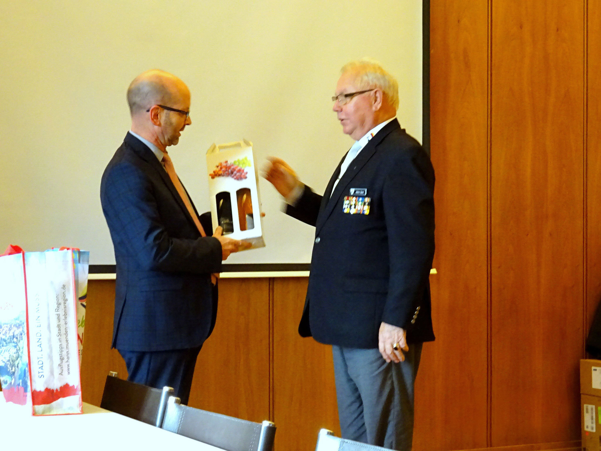 Präsident Heinz Ganz überreicht ein Geschenk an den Bürgermeister Harald Wegener.