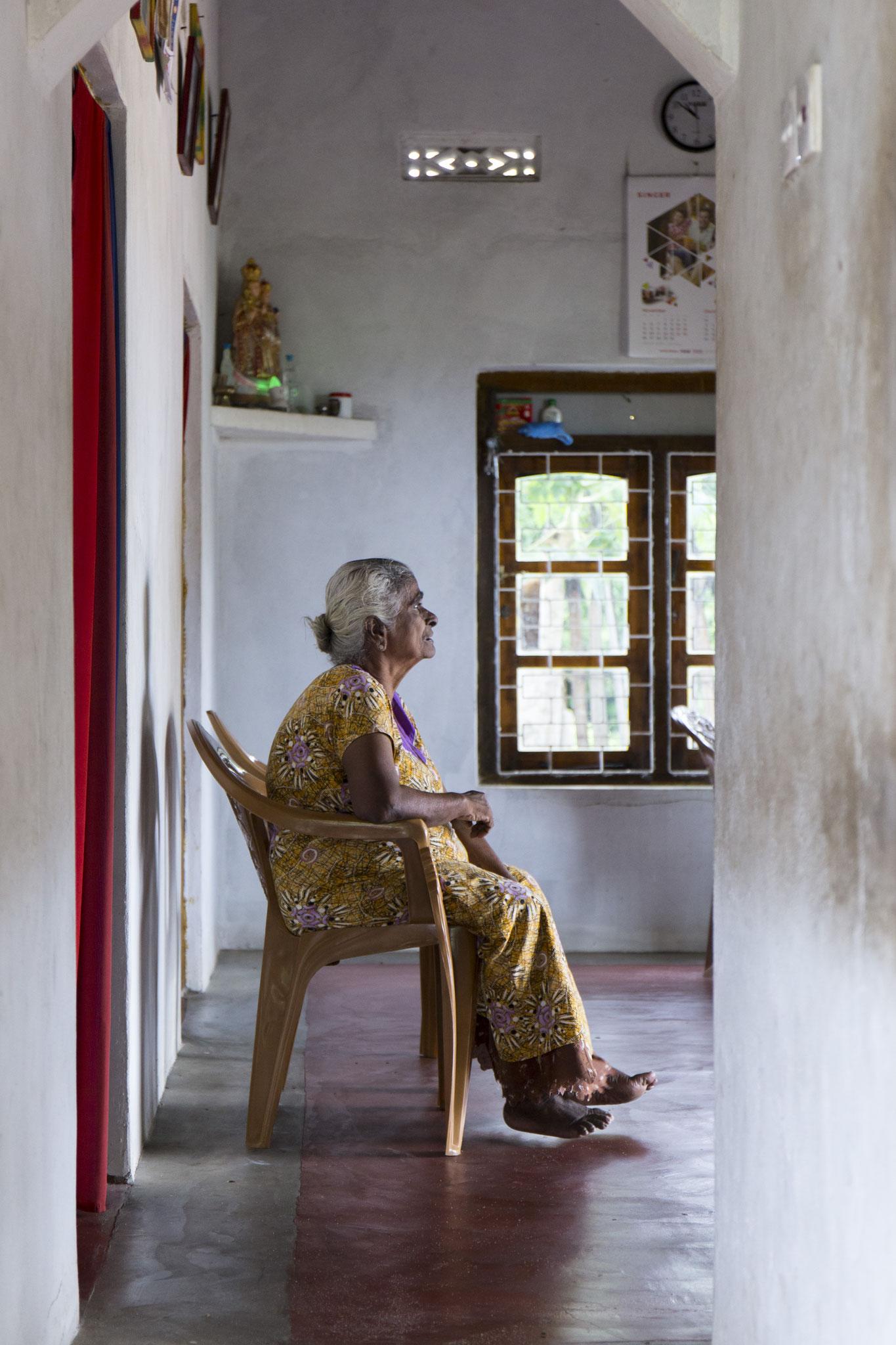 Amma sitzt auf einem Plastikstuhl. Zu Besucht bei ihrem Adoptivsohn Morris. Mullaitivu, 2018