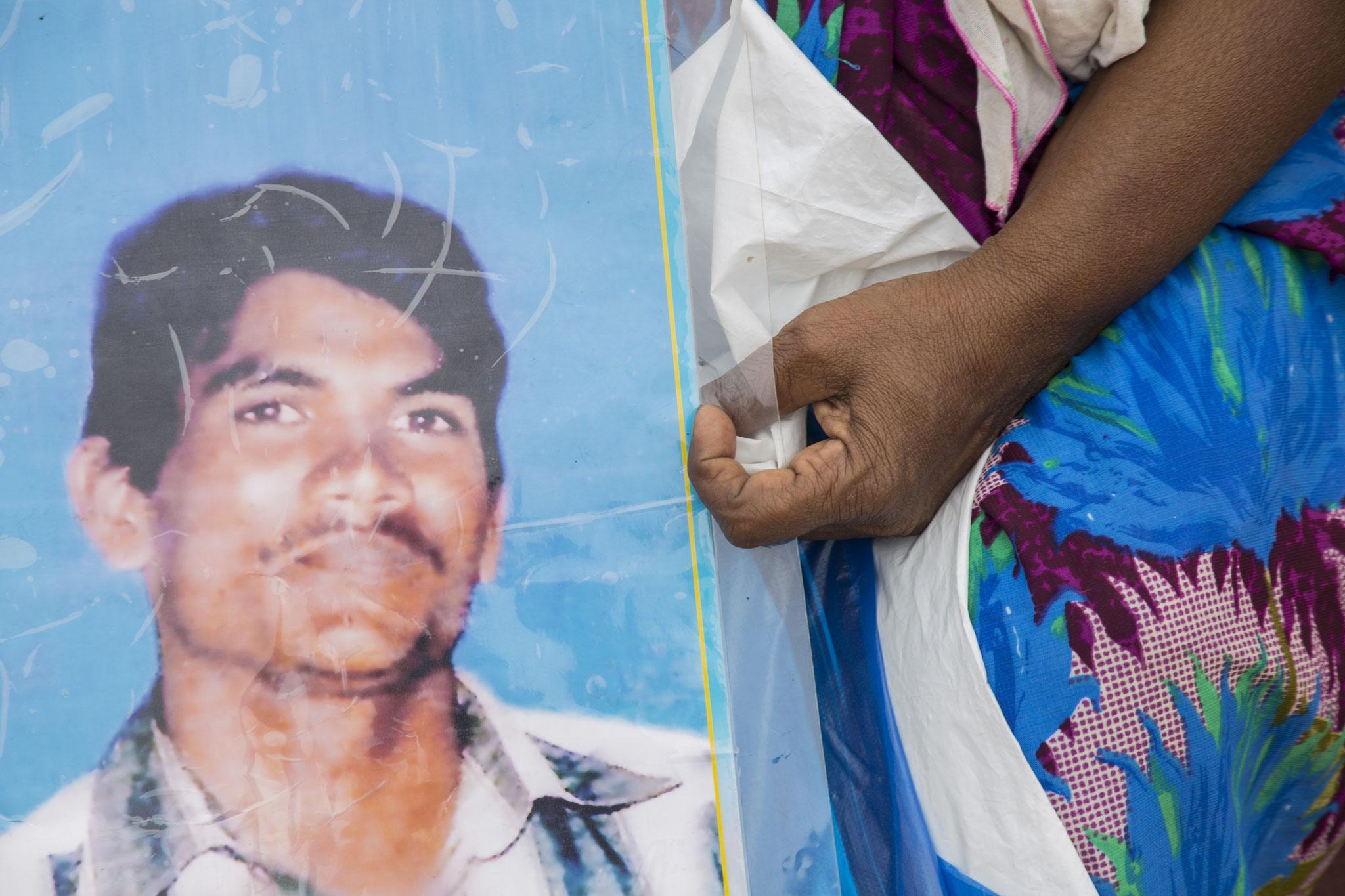 Auf der Demonstration am Human Rights Day hält eine Frau das Bild eines vermissten Familienmitglieds. Mullaitivu, 2018