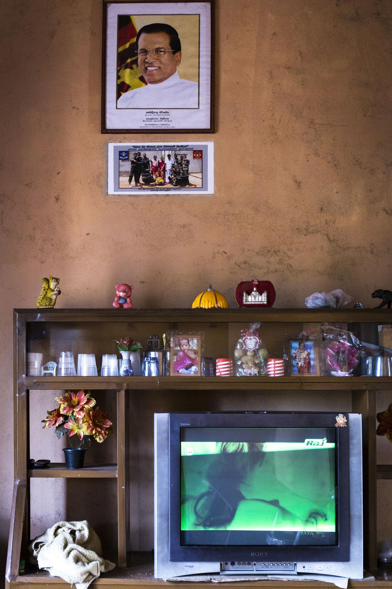 In den Häusern, die die Regierung für die von ihr selbst vertriebenen Familien errichtet hat, ist es Gesetz, dass das Bild des Präsidenten im Wohnzimmer hängt. Direkt darunter ist ein Bild in die Wand eingelassen, auf dem die Soldaten zu sehen sind, die