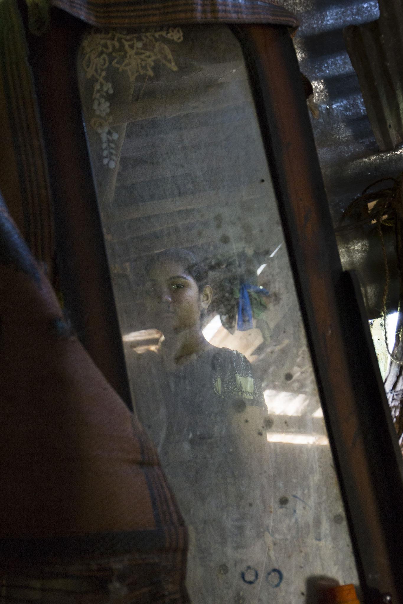 Annalaxmis 16-jährige Tochter schaut in einen dreckigen Spiegel in ihrer Lehnhütte. Vavuniya, 2018