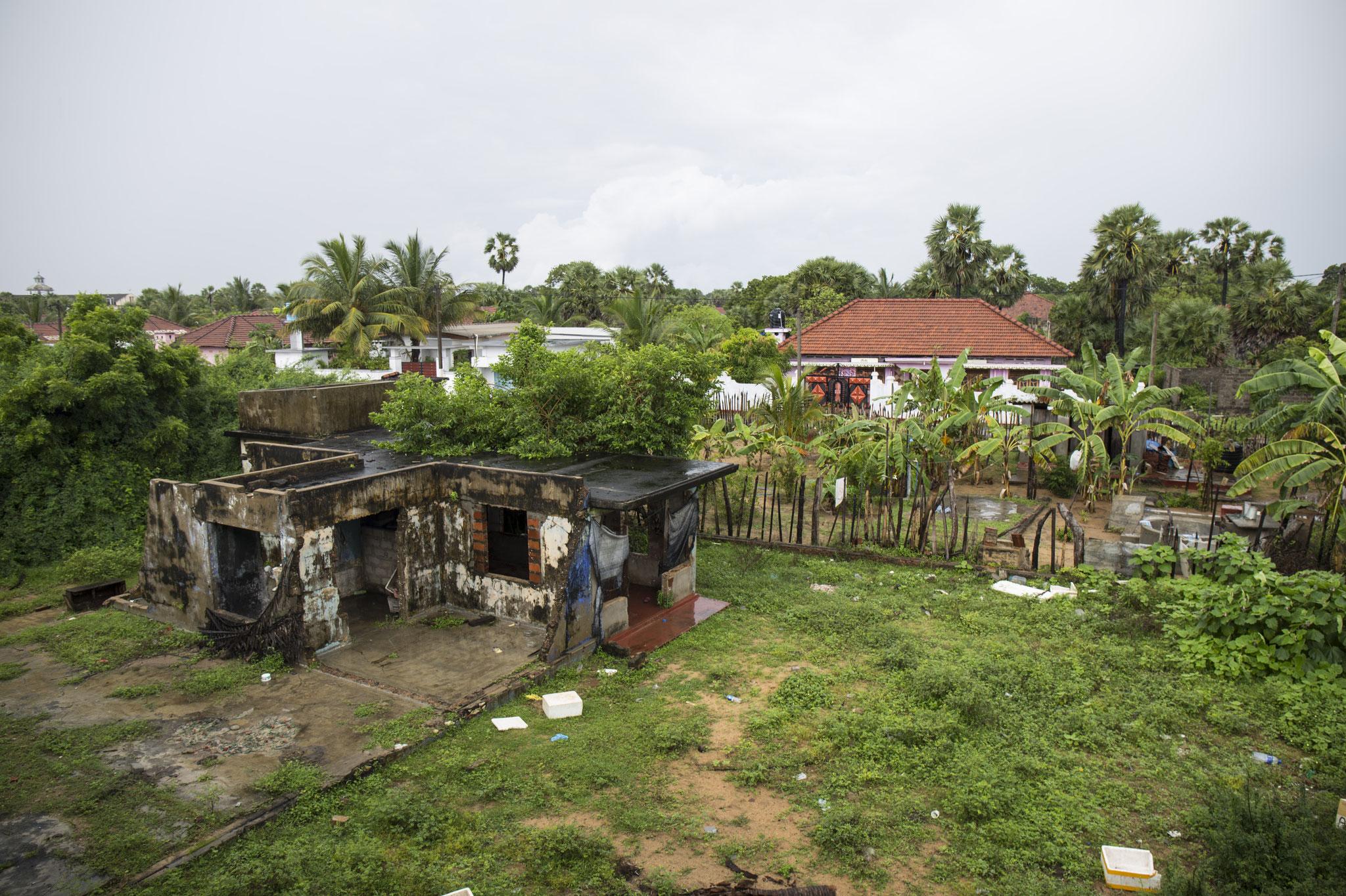 Der Blick aus dem Gasthaus »White House« von Amma zeigt eine ausgebrannte Ruine. Mullaitivu, 2018