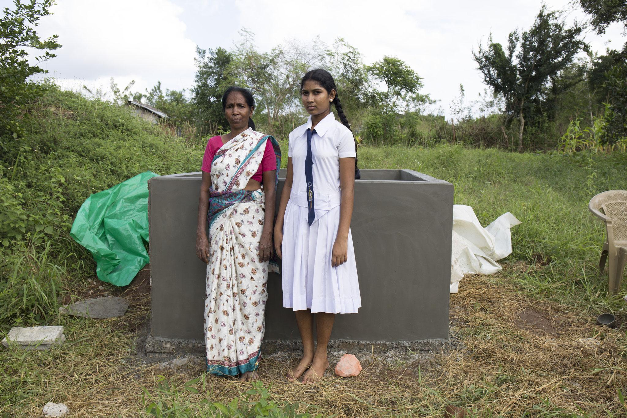 Annalaxmi und ihre 16-jährige Tochter vor einem halbfertigen Brunnen in ihrem Garten. Vavuniya, 2018