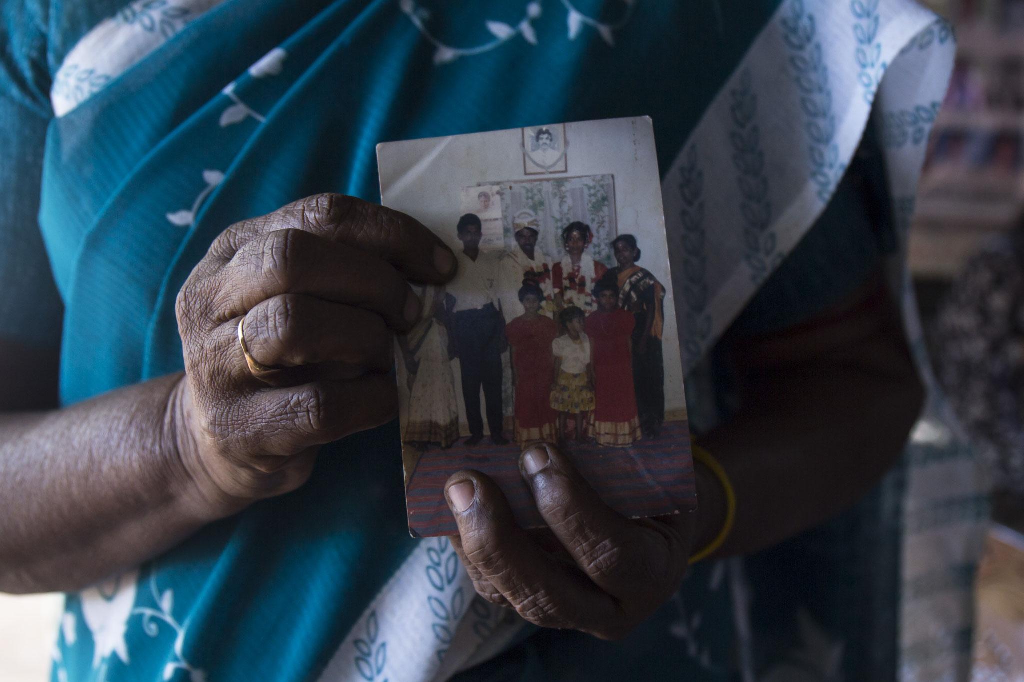 Eine Frau in einem Protestcamp hält ein Familienbild und zeigt auf ihren Sohn, den sie seit dem Bürgerkrieg vermisst. Vavuniya, 2018