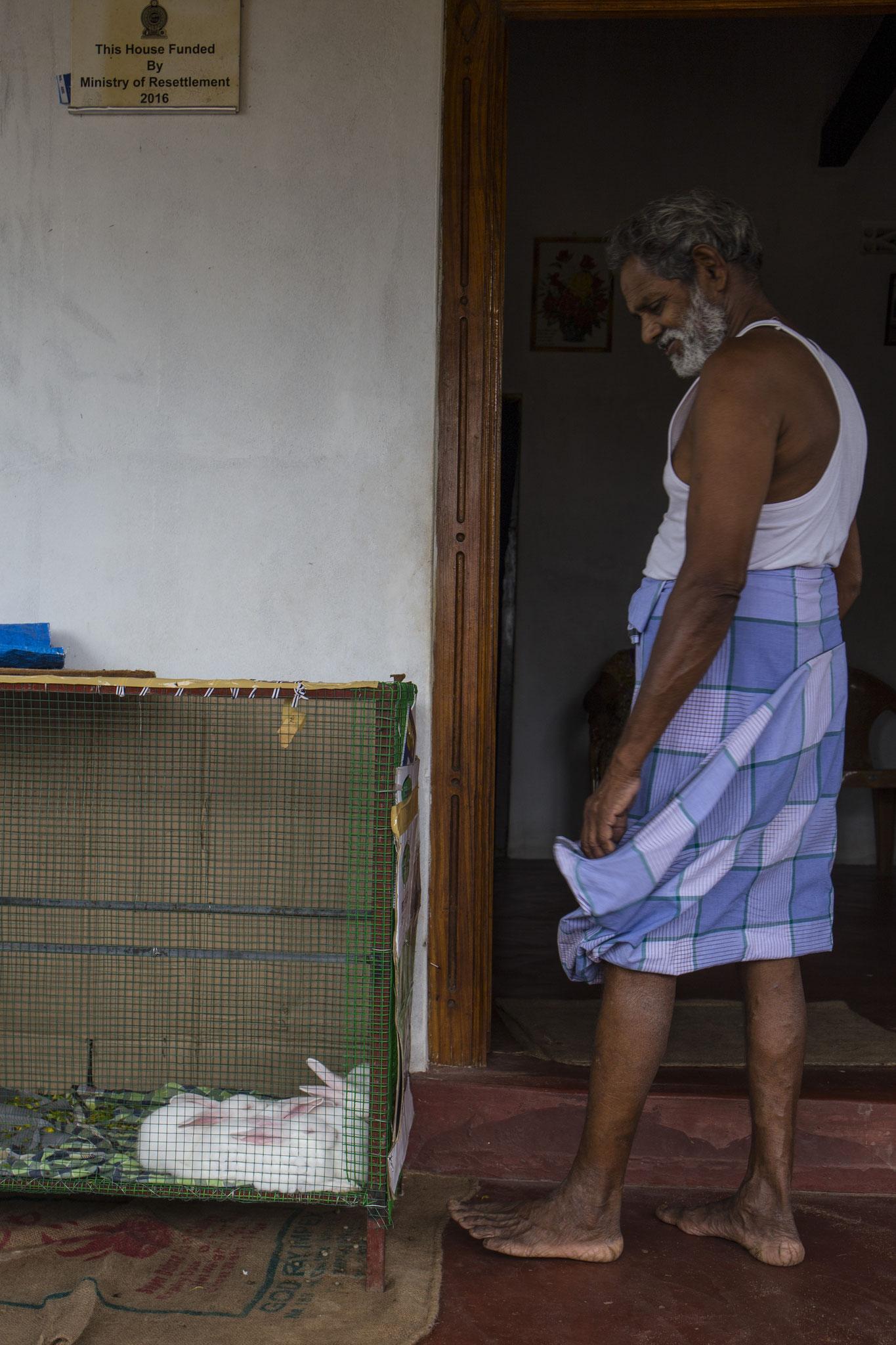 Morris auf seiner Terrasse mit seinen Zuchtkaninchen, mit denen er sich nebenbei etwas Geld verdient. Mullaitivu, 2018