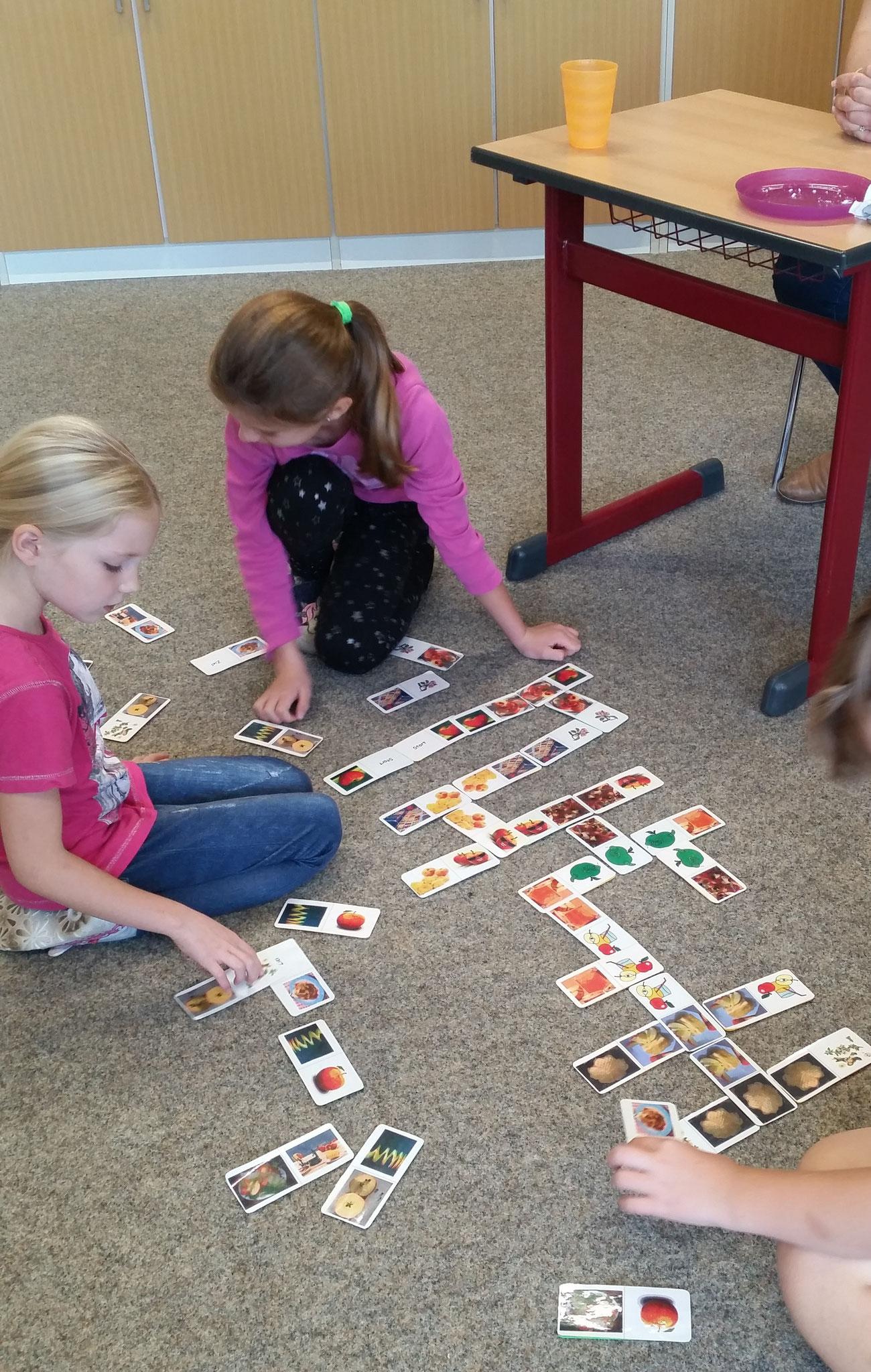 Lia und Lea spielen das Apfel- Domino.