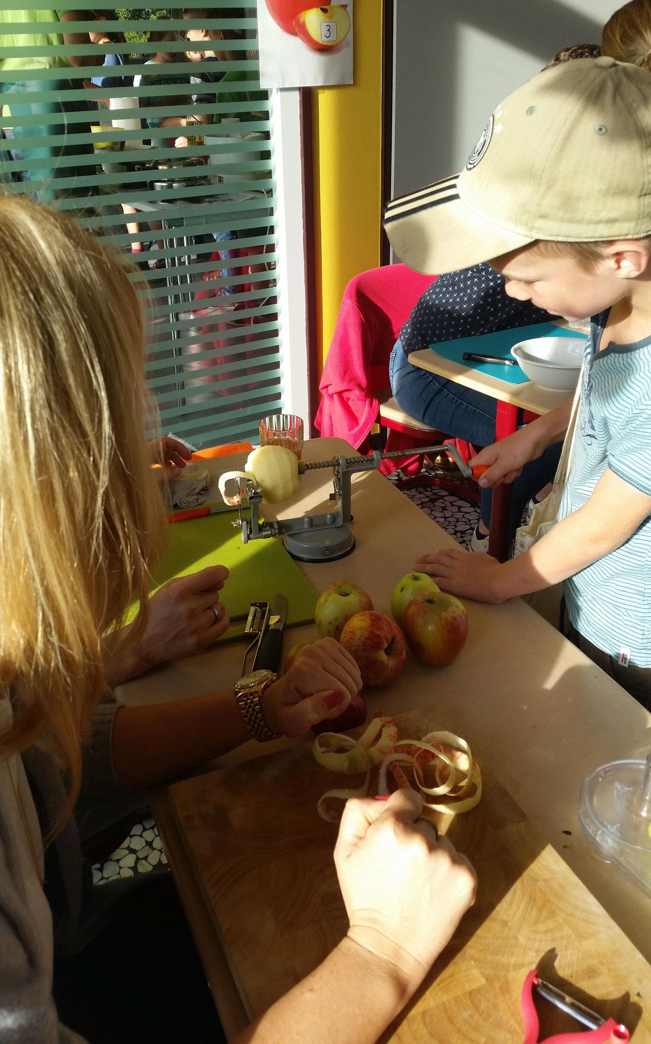 Luis schält den Apfel mit der Schälmaschine und zerlegt ihn in eine lange Spirale.