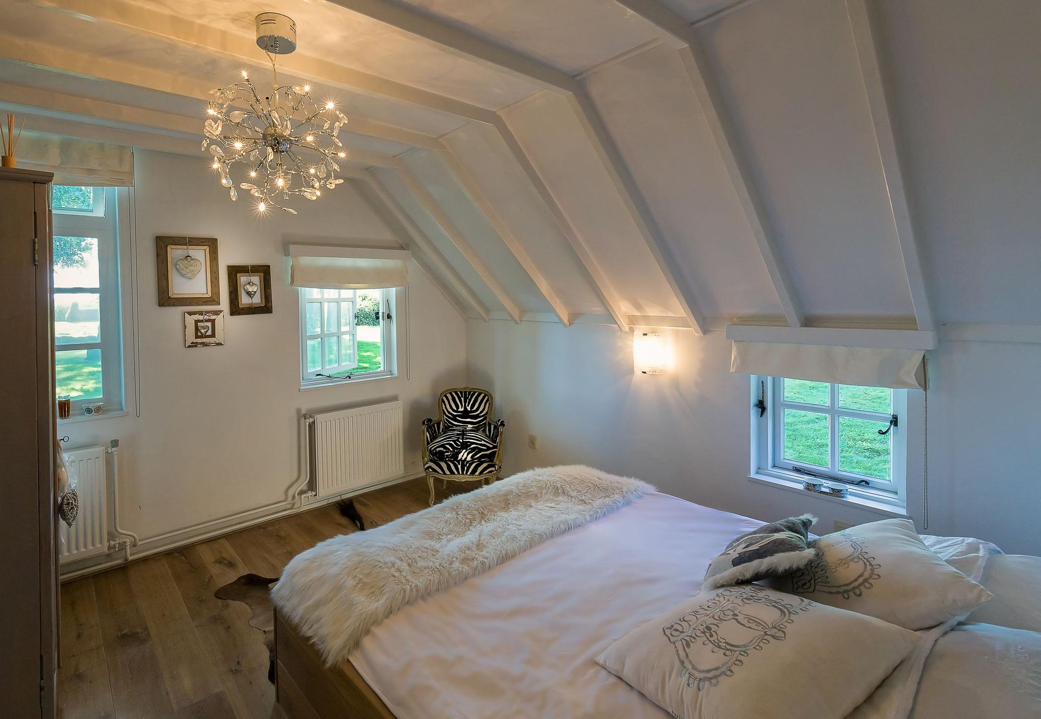 De master bedroom op de begane grond met fabelachtig uitzicht op de vis- en zwemvijver