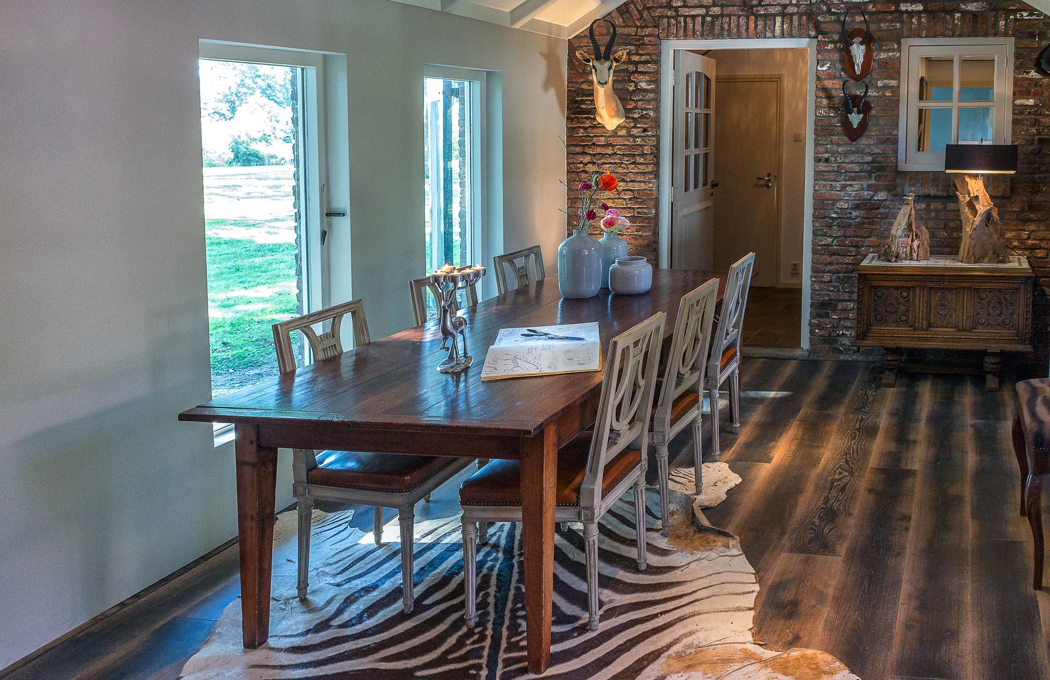 De ruime eetkamer met uitzicht op het landgoed.