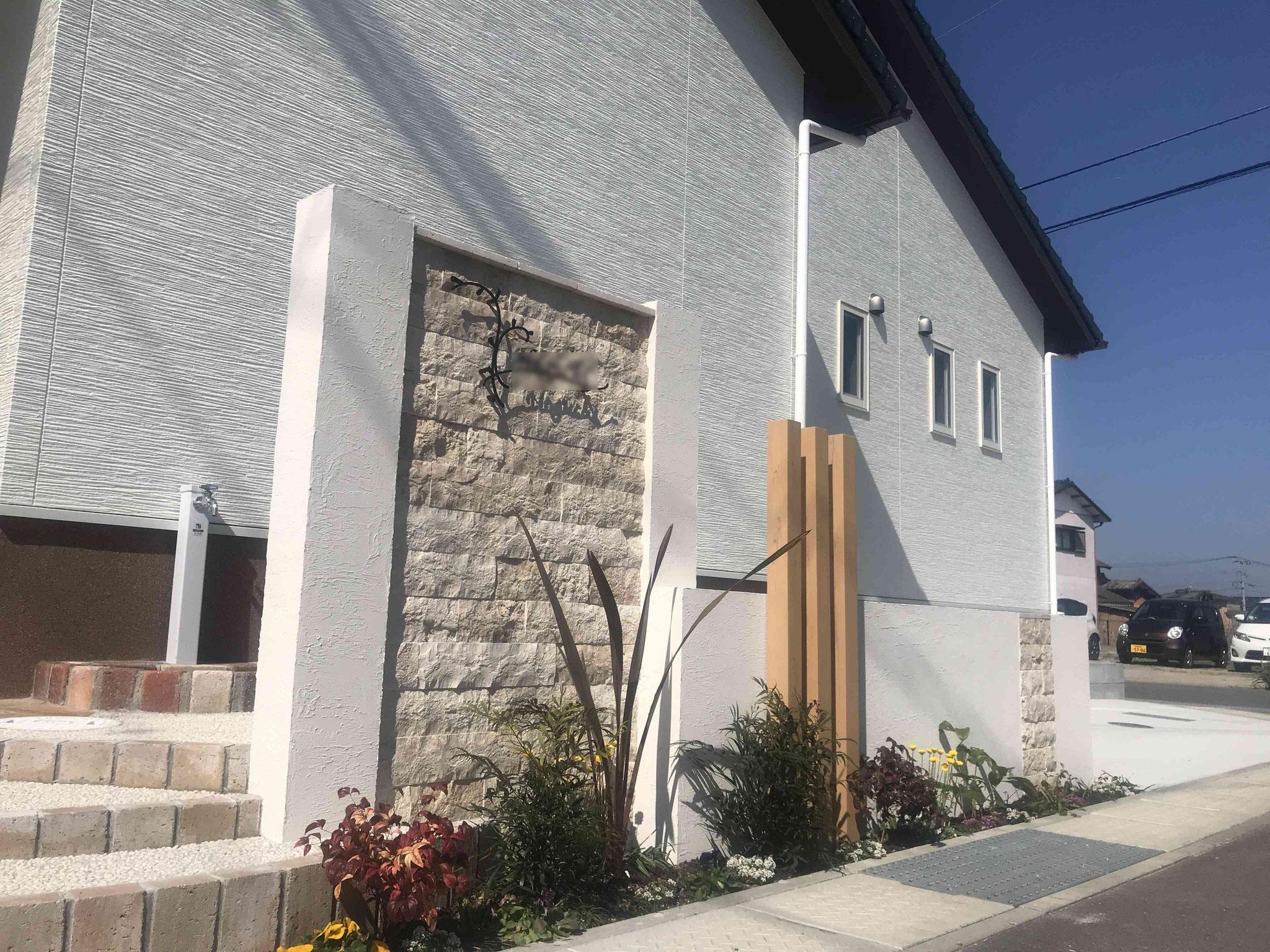白の塗り壁と石張が素敵な門周り