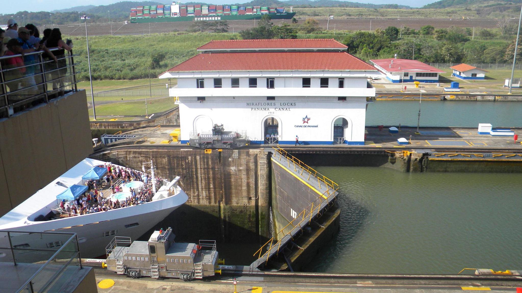 ein großes Containerschiff passiert im Hintergrund die größere neue Schleuse