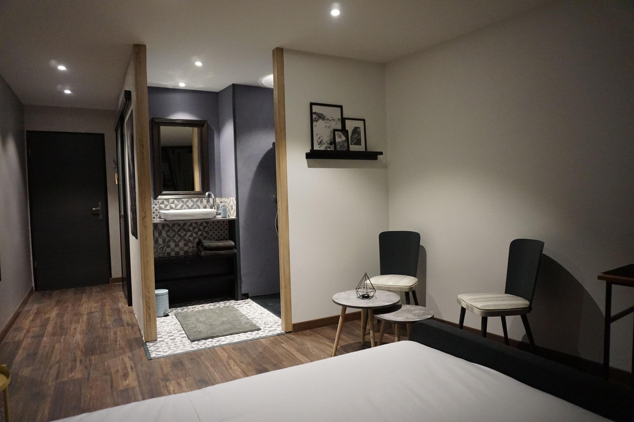 """Gîte """"Les Cépages"""", vue intérieure de la Chambre """"Minérale"""" : lit, espace de vie, salle de bain, entrée"""
