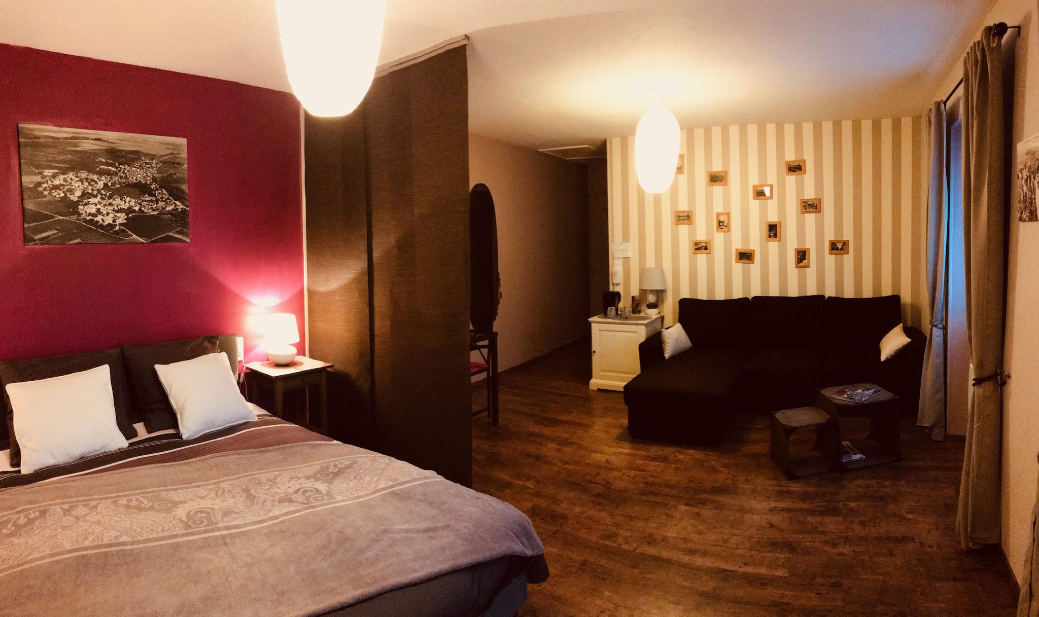 """Gîte """"Les Cépages"""", vue intérieure de la Chambre """"Pinot Noir"""" : lit, espace de vie (canapé convertible, minibar)"""