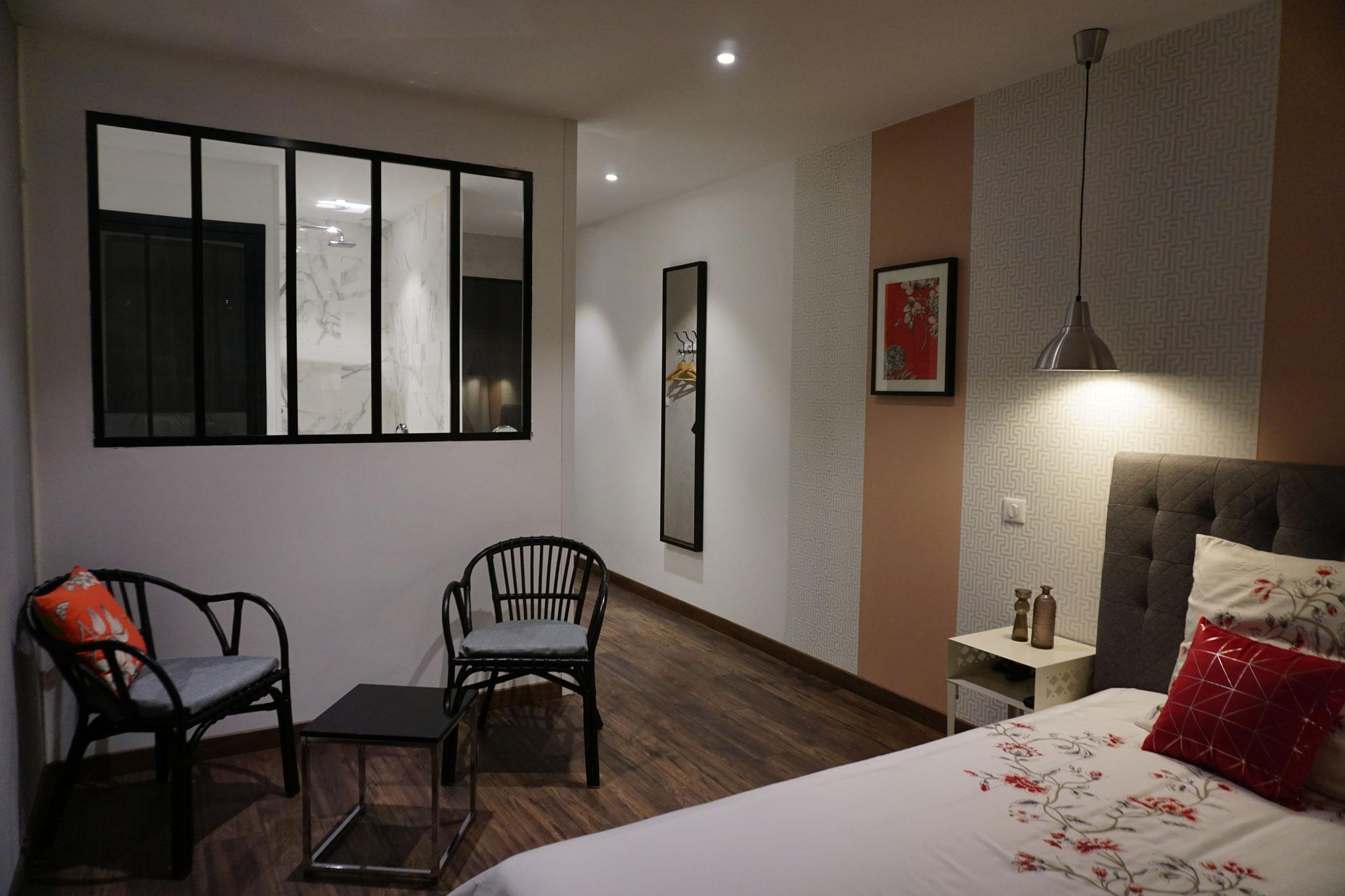 """Gîte """"Les Cépages"""", vue intérieure de la Chambre """"Fleurie"""" : lit, espace de vie, entrée"""