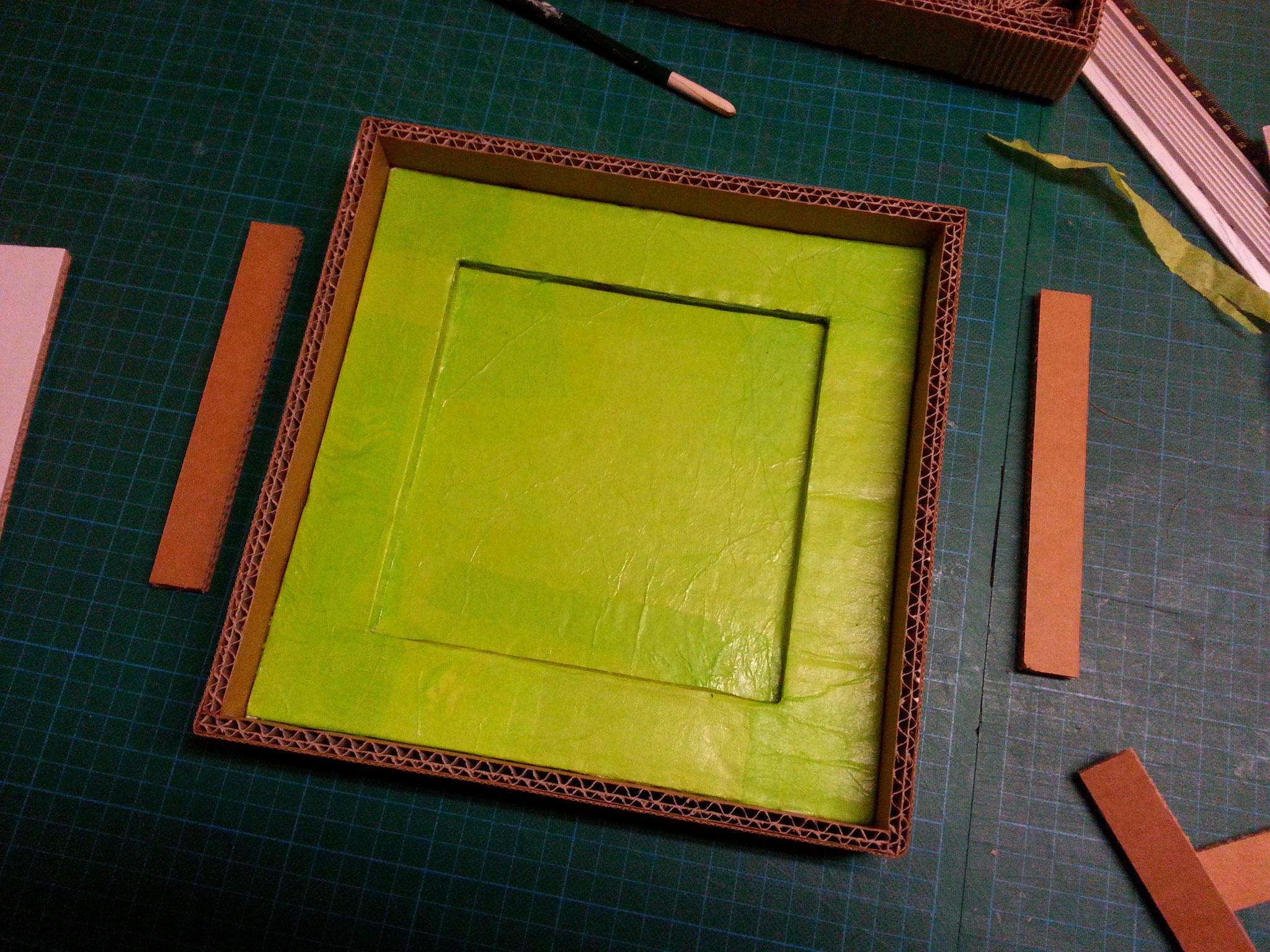 Le carton est recouvert de papier de soie, pose des bordures pour délimiter le cadre.