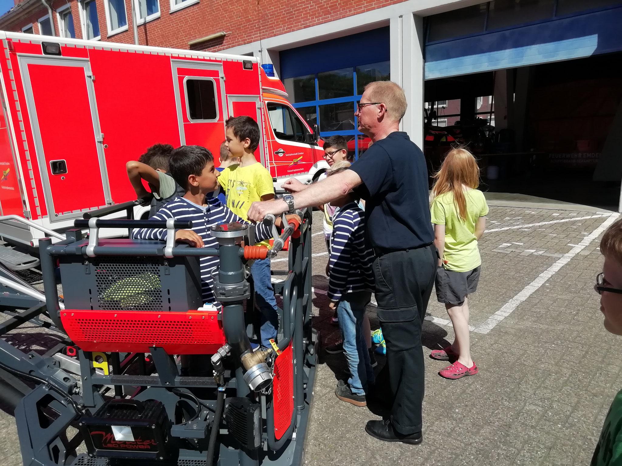 Herr Akkermann erklärt, dass zur Aufnahme in der Feuerwehr jeder Bewerber oder jede Bewerberin den ausgefahrenen Leiterwagen hochklettern muss.